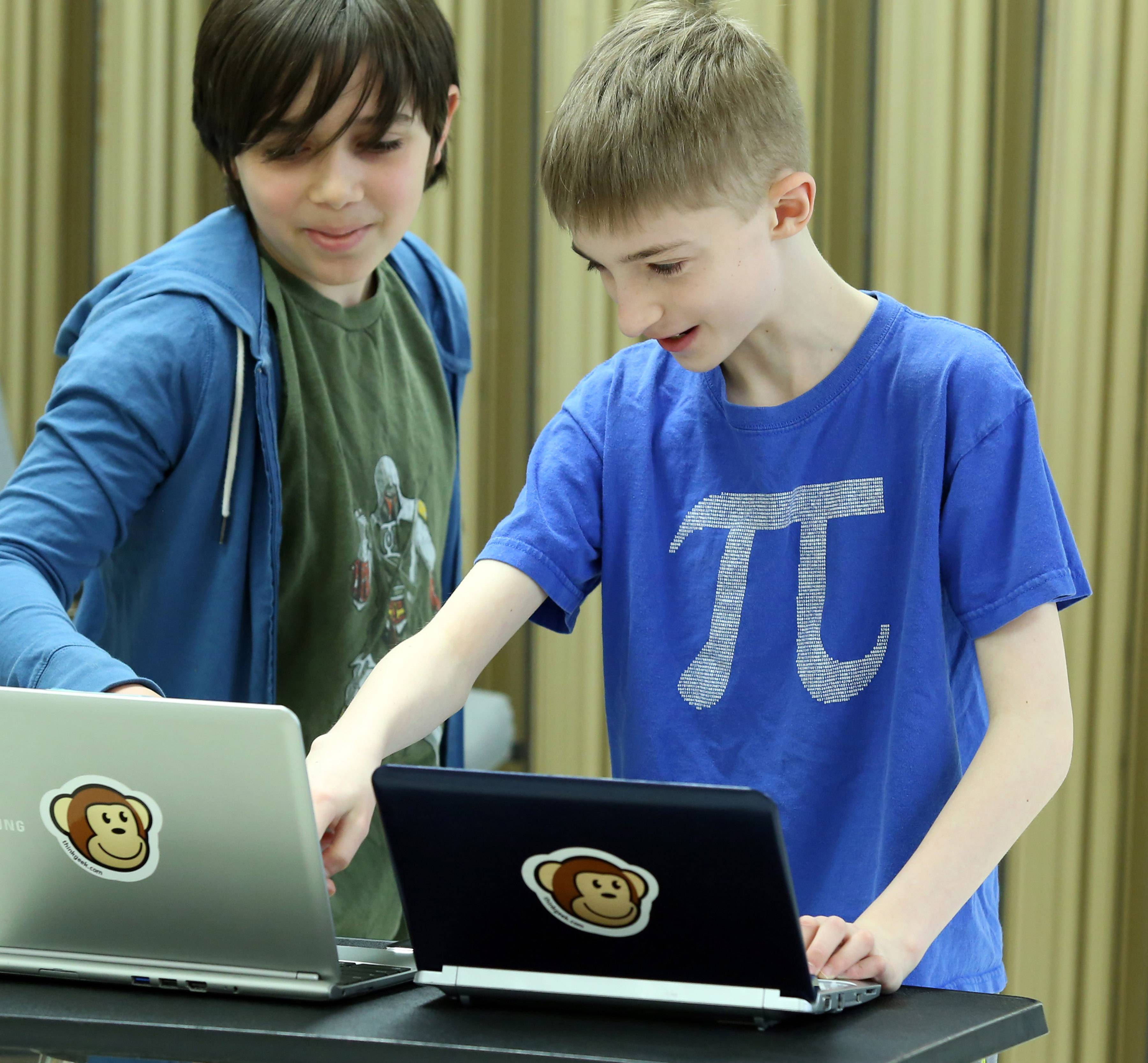 Andy Merrill, 13, of Libertyville, wearing his favorite T-shirt, pi, discusses a new programing language he is using on his laptop with Asher Hoeveler, 11, of Evanston, left, during a Curiosity Hacked Guild meeting.