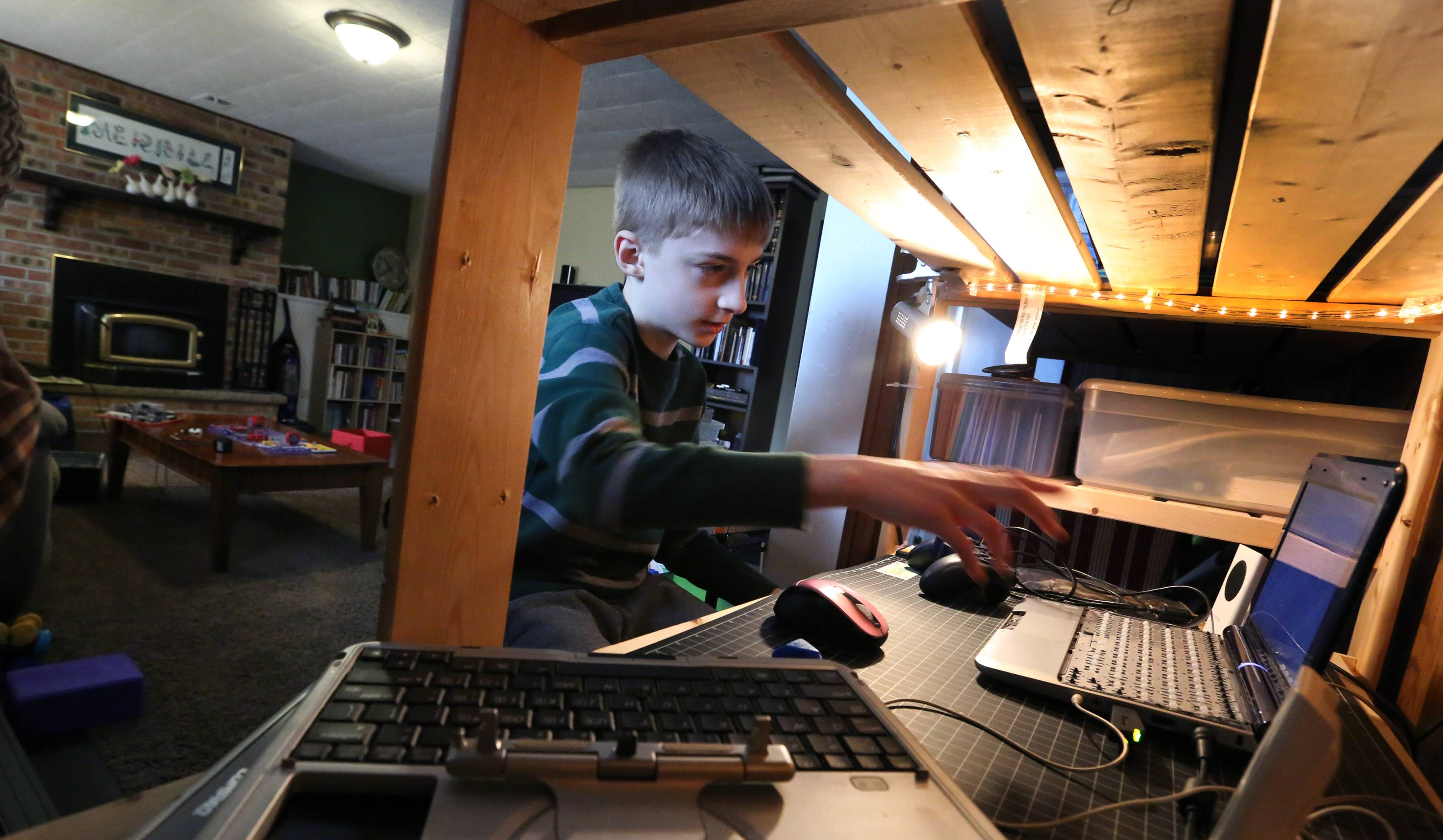 Andy Merrill opens a program on his laptop at his Makerspace workstation that his mom, Jenny, created for him to work on projects.