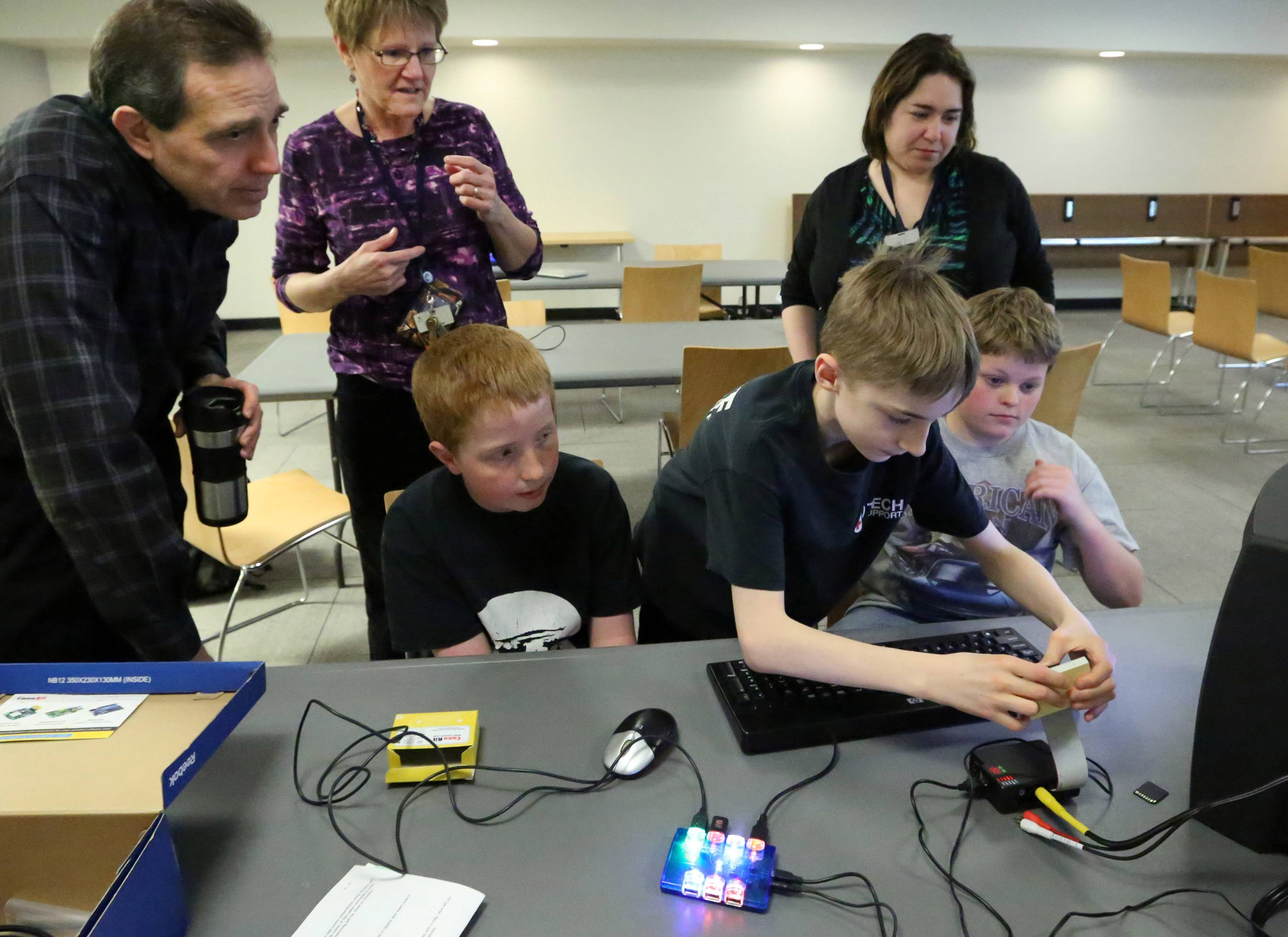 "Andy Merrill, 13, of Libertyville, connects a monitor and keyboard to a Raspberry Pi, a credit-card sized computer, during a teen program called ""Teen Tinkers and Minecraft"" at Cook Park Library. With him, left to right standing, are Russ Cerqua, the library's business manager, Ellen Jennings, teen librarian, and Heather Beverley, assistant manager in the children's department, along with members of the teen group."