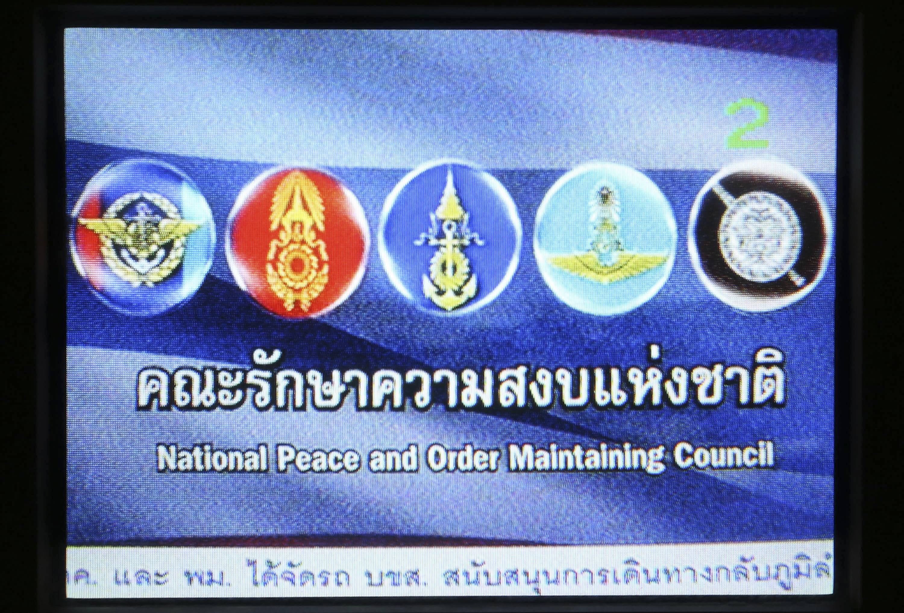 Thailand's junta has commandeered every TV channel for round-the-clock broadcasts of dour announcements and patriotic hymns backed by this blue screen with military crests. The public's verdict: DJ, please change the soundtrack.