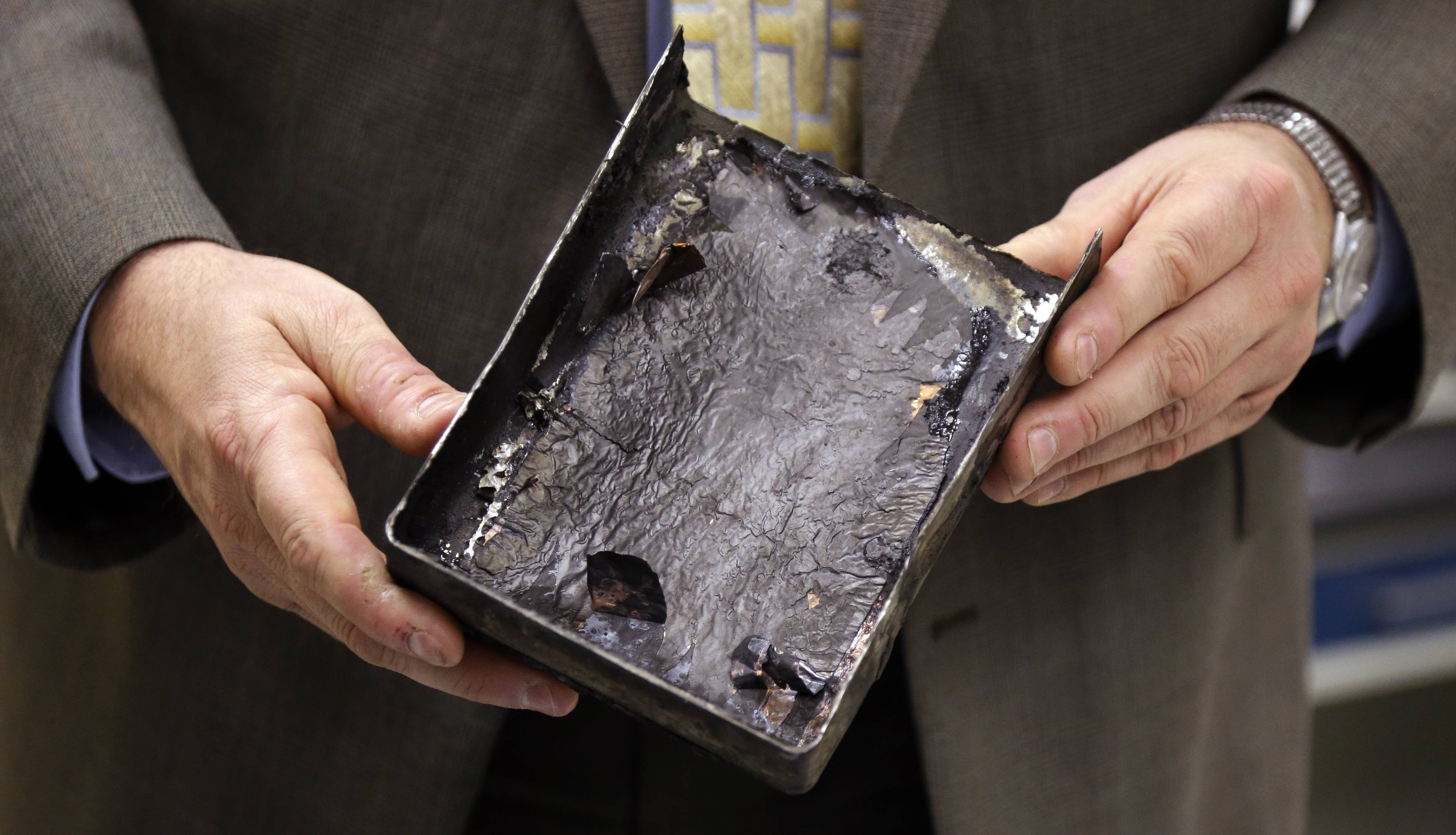 In this Jan. 24, 2014 photo, National Transportation Safety Board's Joseph Kolly, holds a fire-damaged battery casing from the Japan Airlines Boeing 787 Dreamliner that caught fire at Logan International Airport in Boston.