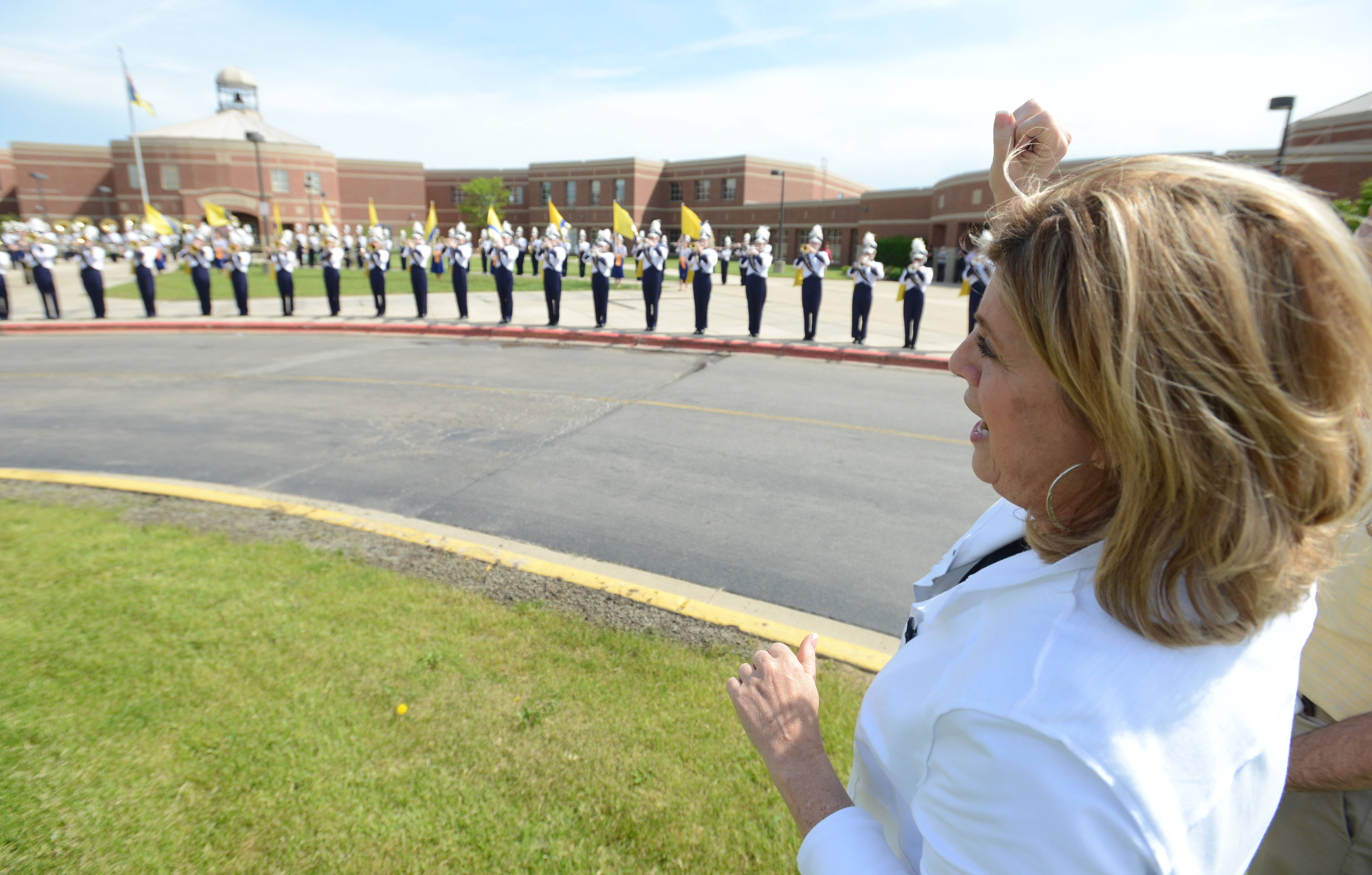 Indian Prairie Unit District 204 Superintendent Kathy Birkett cheers along to the Neuqua Valley High School fight song as the marching band welcomes her Thursday afternoon to the school where she served as founding principal. Birkett will retire Friday after 35 years with the district.