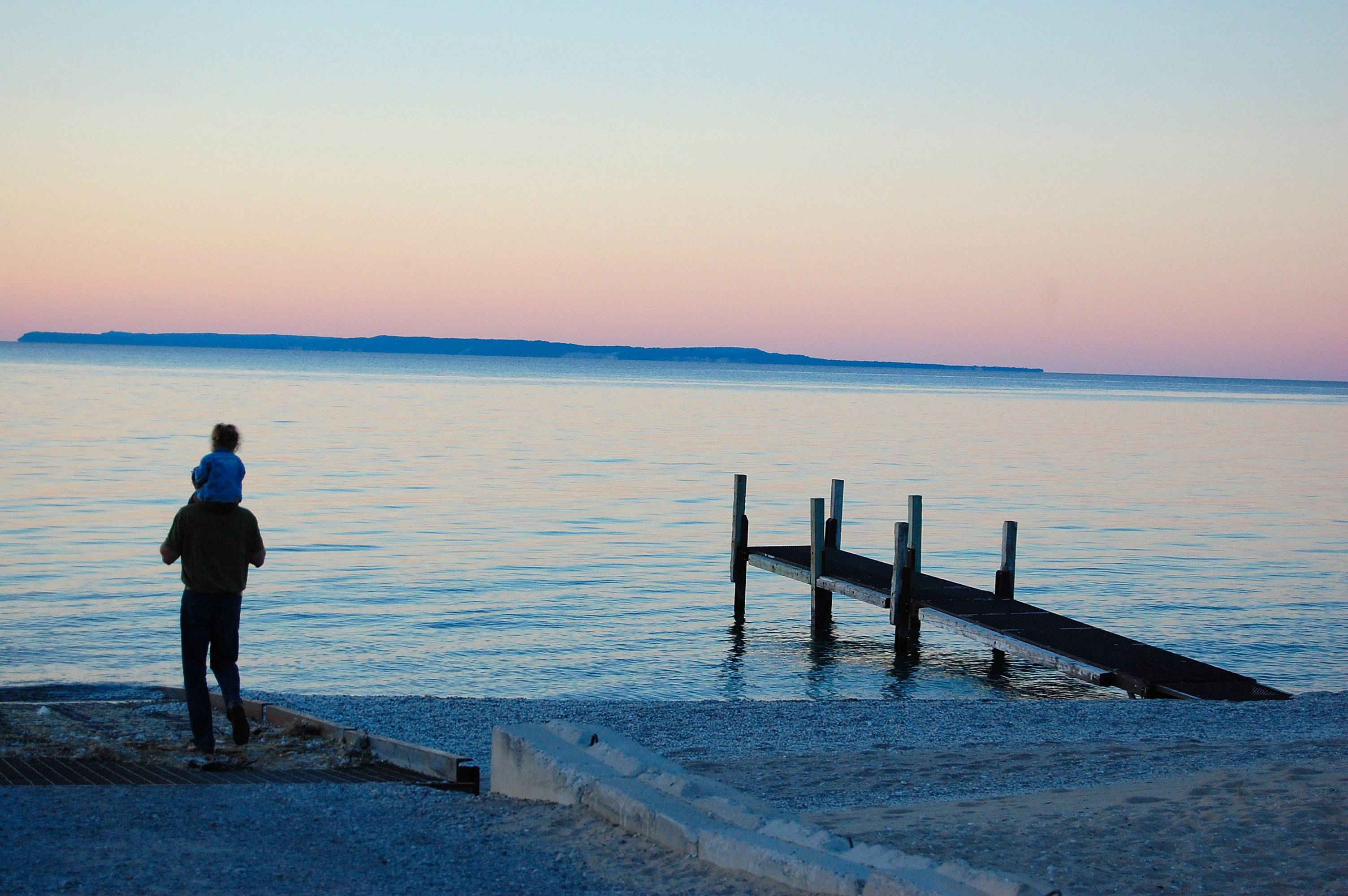 A father and his daughter watch the sun go down along the shore in Glen Arbor, Michigan.