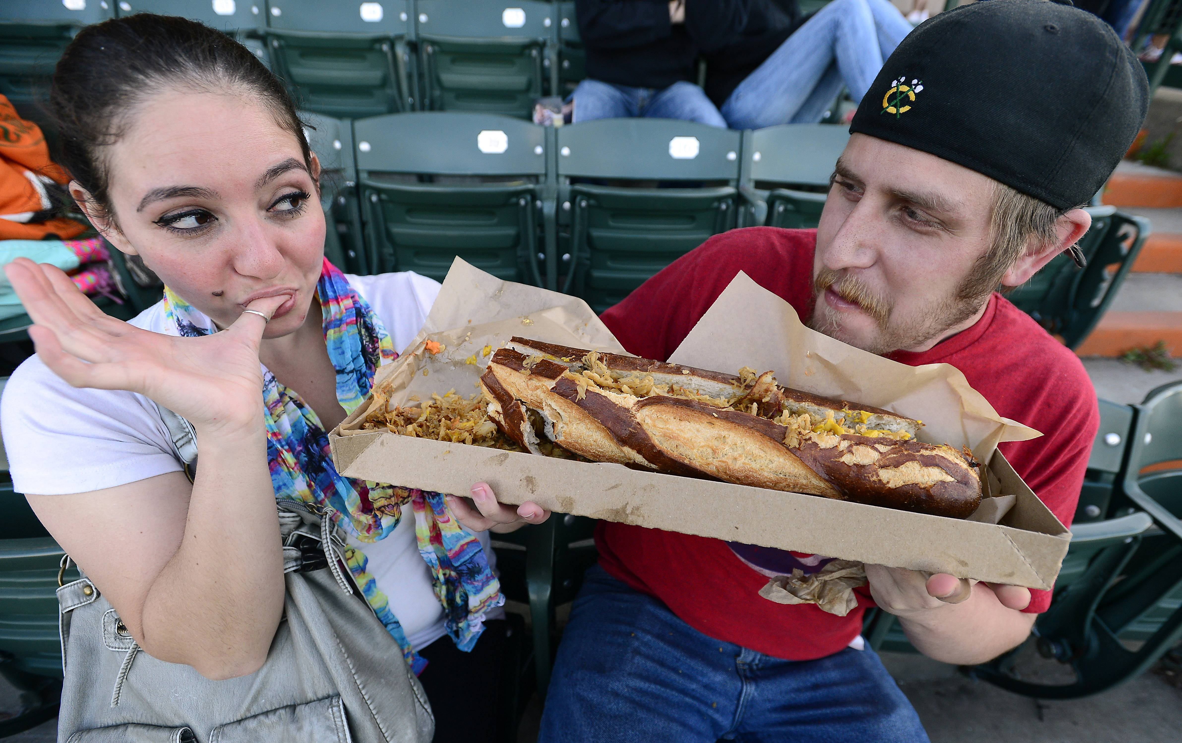 Mark Welsh/mwelsh@dailyherald.comSchaumburg Boomers fans Bianca Bacarella of Chicago and Bob Curth of Elk Grove tackle a monster sandwich at the ball park on opening night against the Florence Freedom to a packed house on Friday.