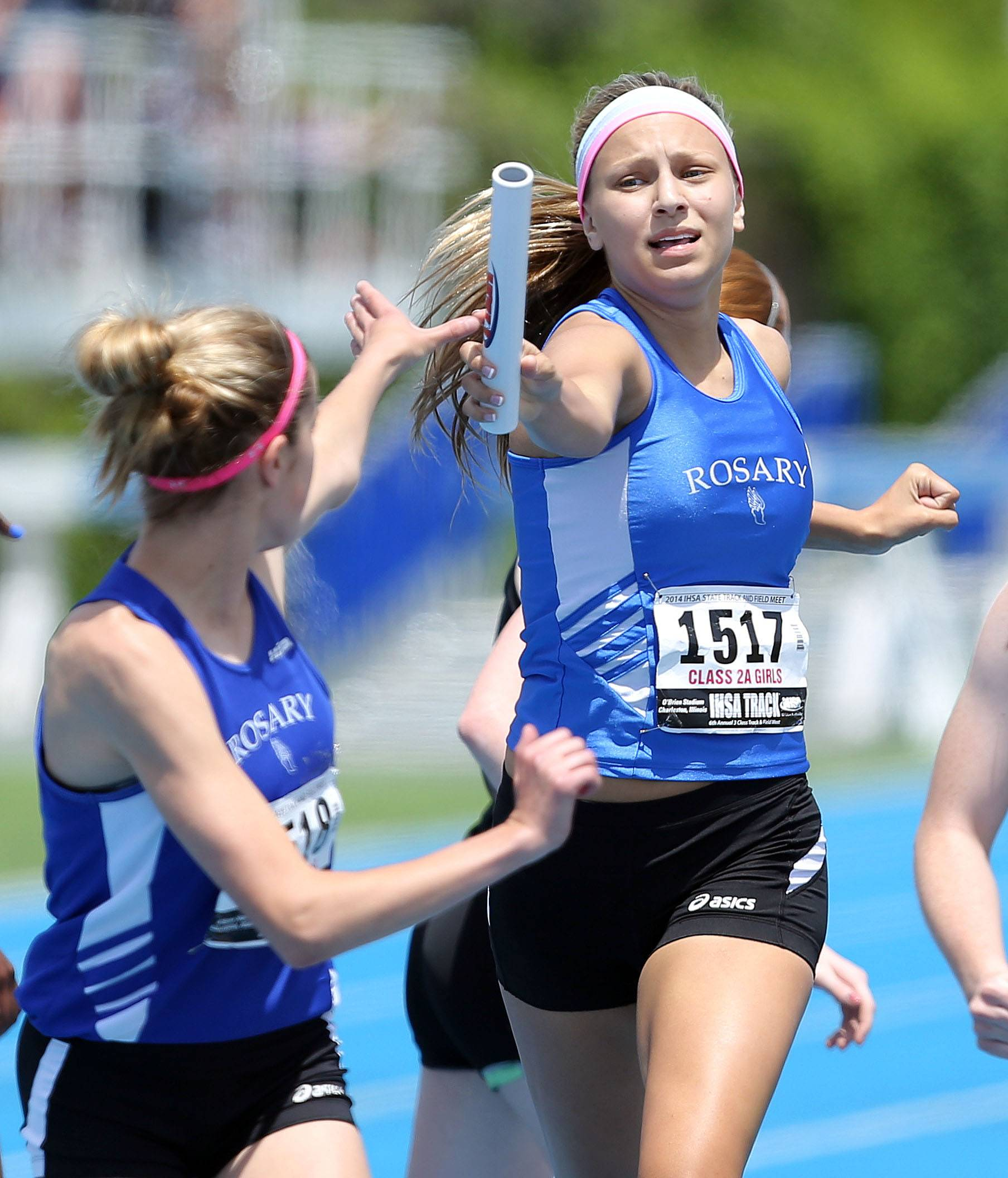 Rosary's Shea Vero, left, takes the baton from Molly Stefanski in the 4x400-meter relay during the prelims of the girls track and field state meet at Eastern Illinois University in Charleston Friday.