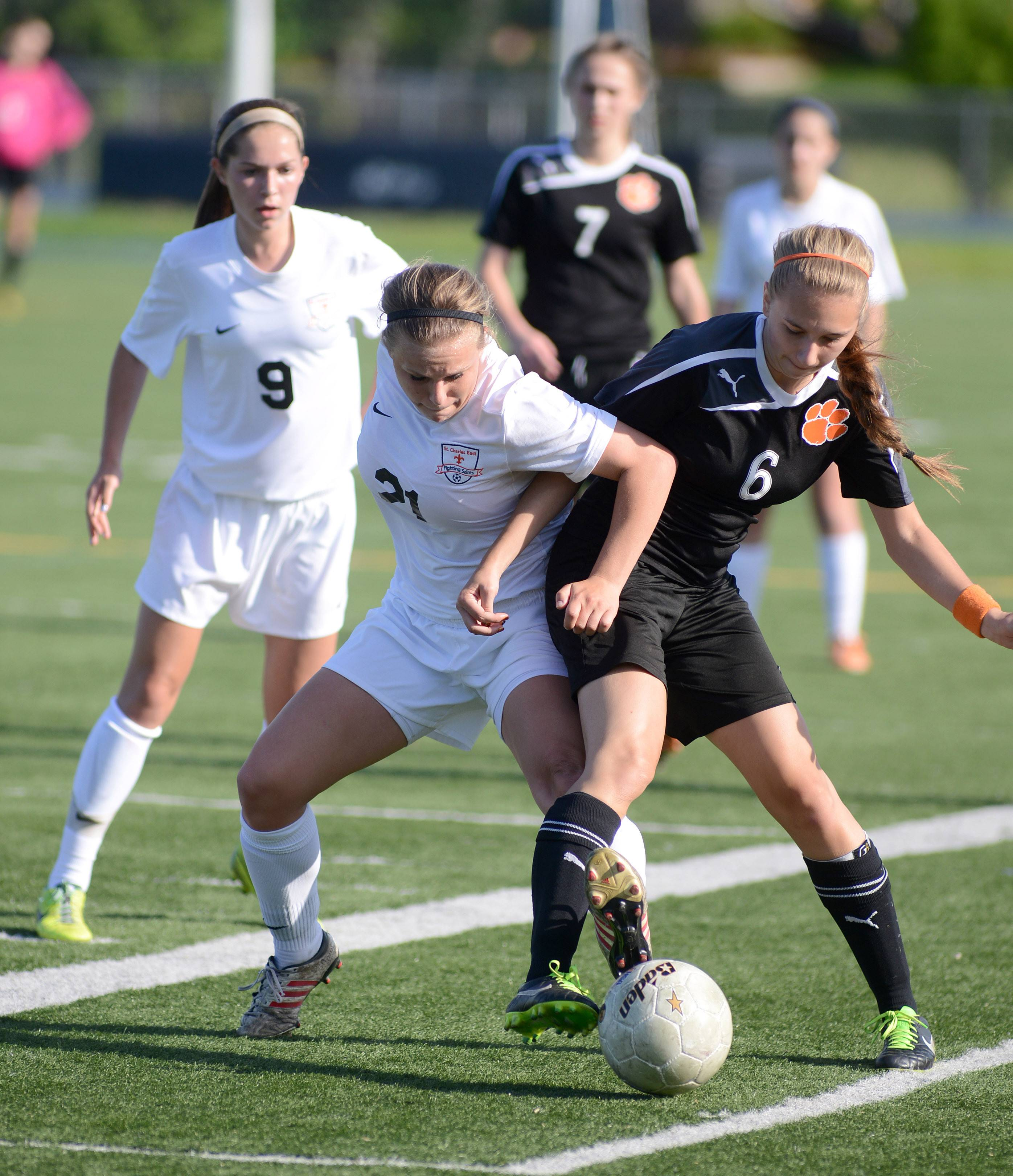 St. Charles East's Amanda Hilton, left, and Wheaton Warrenville South's Marina Tolczyk battle for the ball near the boundary line in the first half of the regional title game at West Chicago High School on Friday, May 23.