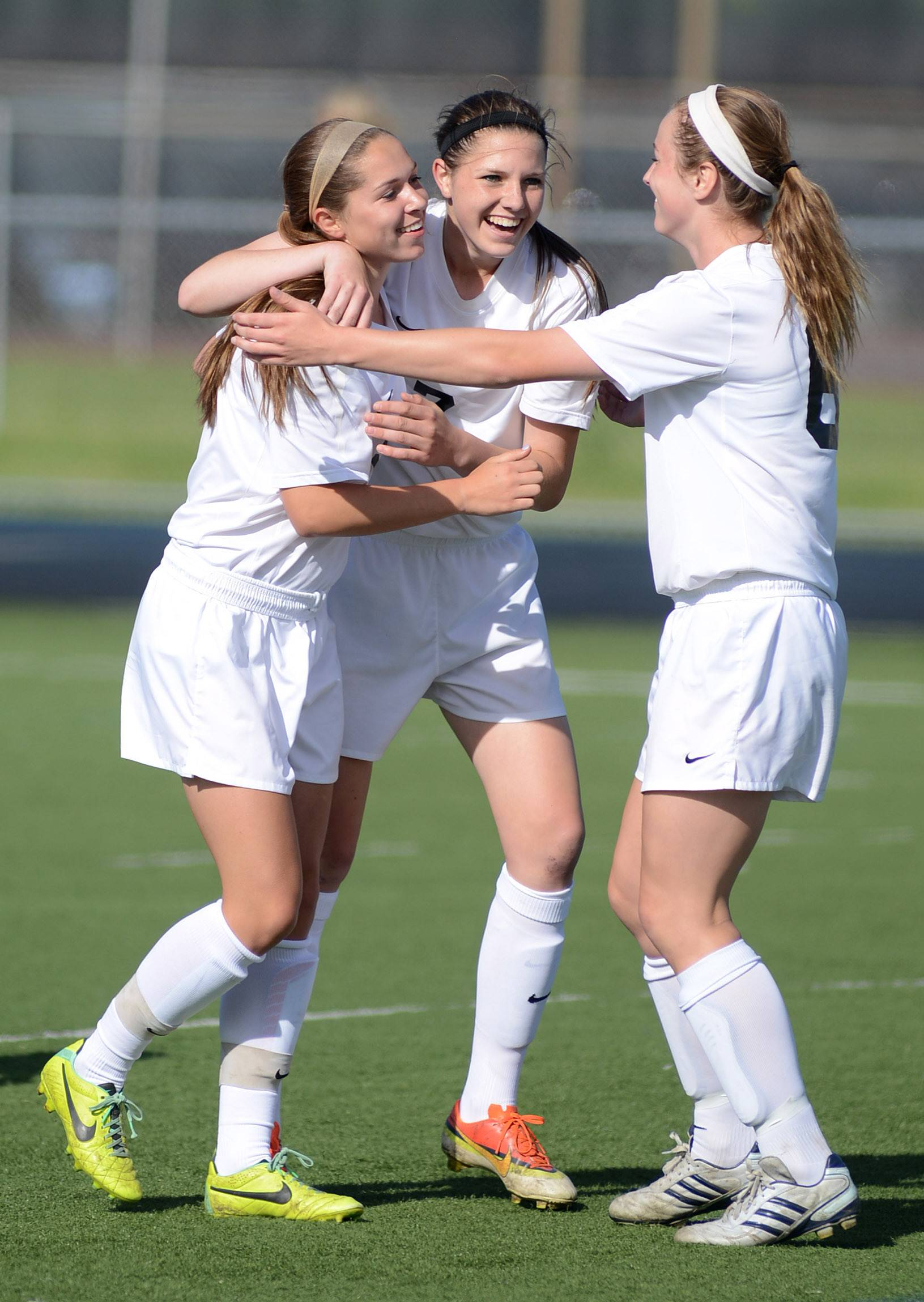 St. Charles East's Darcy Cunningham, far left, is congratulated by teammates Rion Gaffney, center, and Kelli Santo Paulo, right, after scoring a goal against Wheaton Warrenville South in the first half at West Chicago High School on Friday.