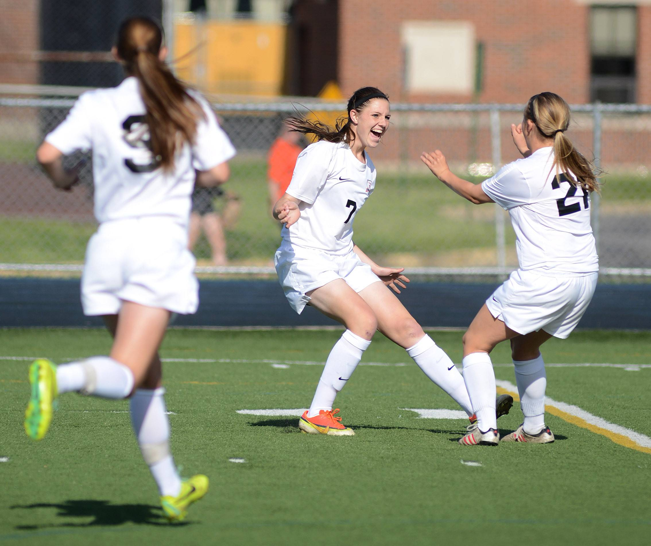 St. Charles East's Rion Gaffney, center, celebrates her goal, and the first for the team, with teammate Amanda Hilton, far right, as Darcy Cunningham runs towards them in the first half of the regional title game at West Chicago High School on Friday, May 23.
