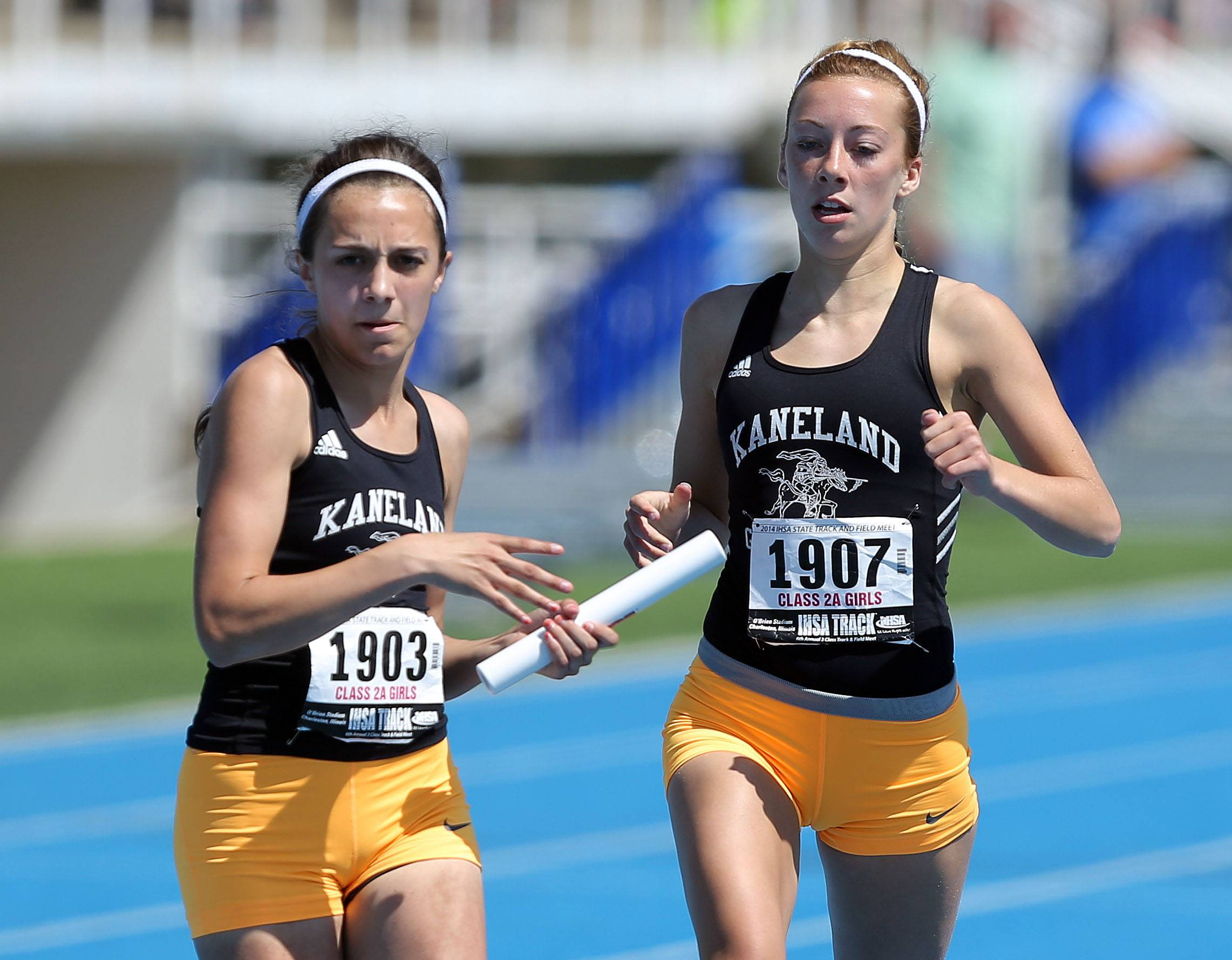 Kaneland's Allie Heinzer, left, takes the baton from Becca Richtman in the 4x200-meter relay in Class 2A.
