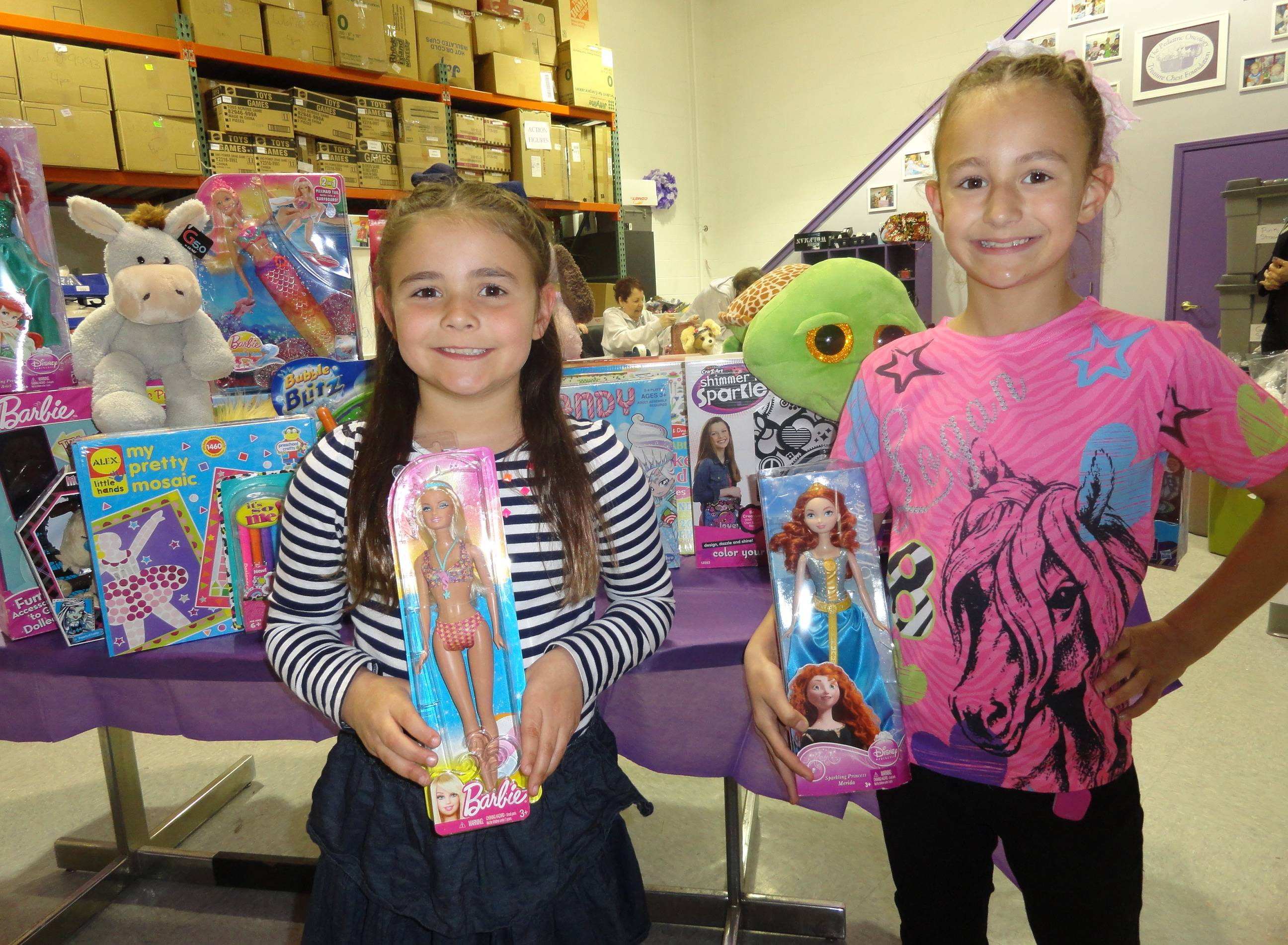 Birthday girl Payton Howard, 7, left, and big sister Logan Howard, 8, display some of the toys Payton collected for the Treasure Chest Foundation at the foundation's Orland Park warehouse. The toys will be given to children and teens battling cancer across the nation.