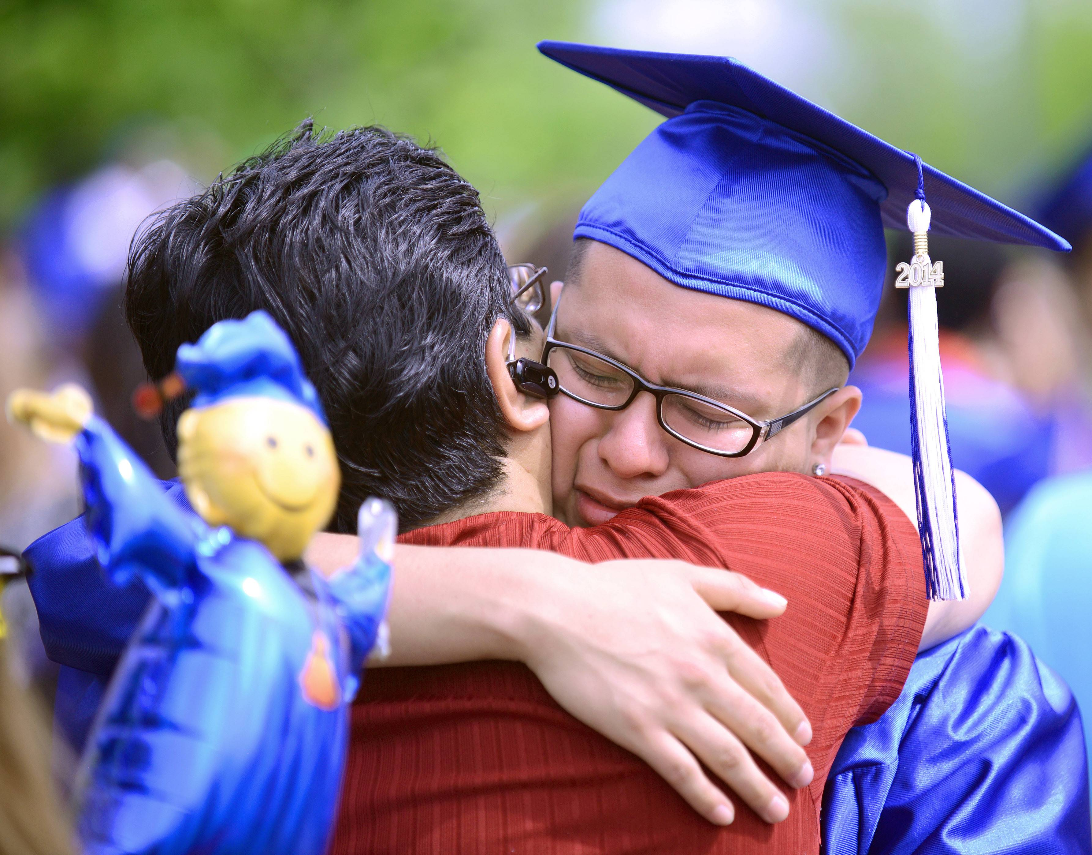 Fernando Garcia of Elgin shares a long, emotional hug with his father, Jorge, after graduating at Larkin High School's commencement ceremony at the Sears Centre in Hoffman Estates on Saturday, May 24.