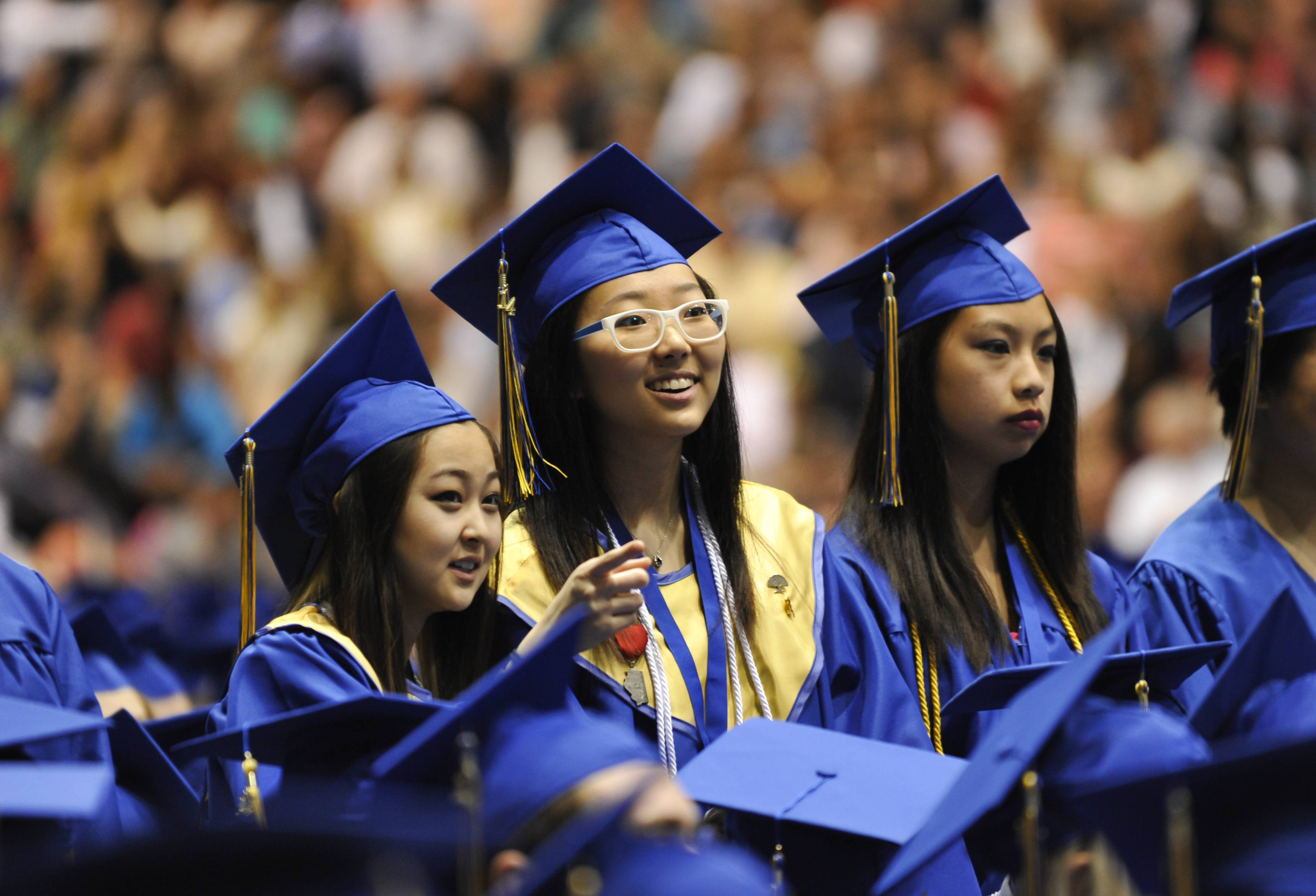 Erica Chau of Park City, Young-Ji Cho of Gurnee, and Jade Gonzales Chua of Gurnee look into the audience during the Warren Township High School commencement at Northwestern University's Welsh-Ryan Arena in Evanston on Saturday, May 24. All three students graduated with honors.