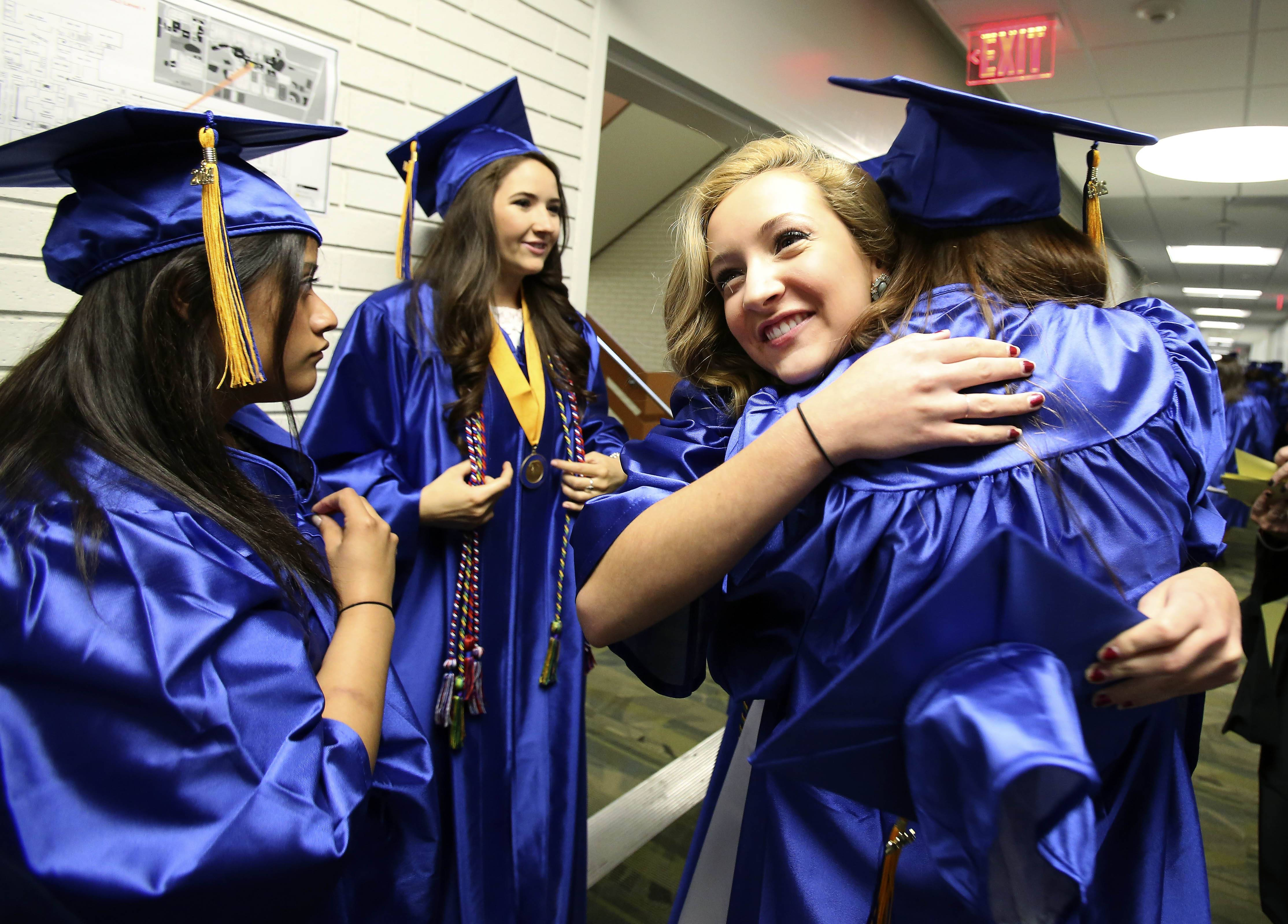 Micheli Venckus, right, gives Jacquelyn Spathies a hug before the Wheaton North High School graduation ceremony .