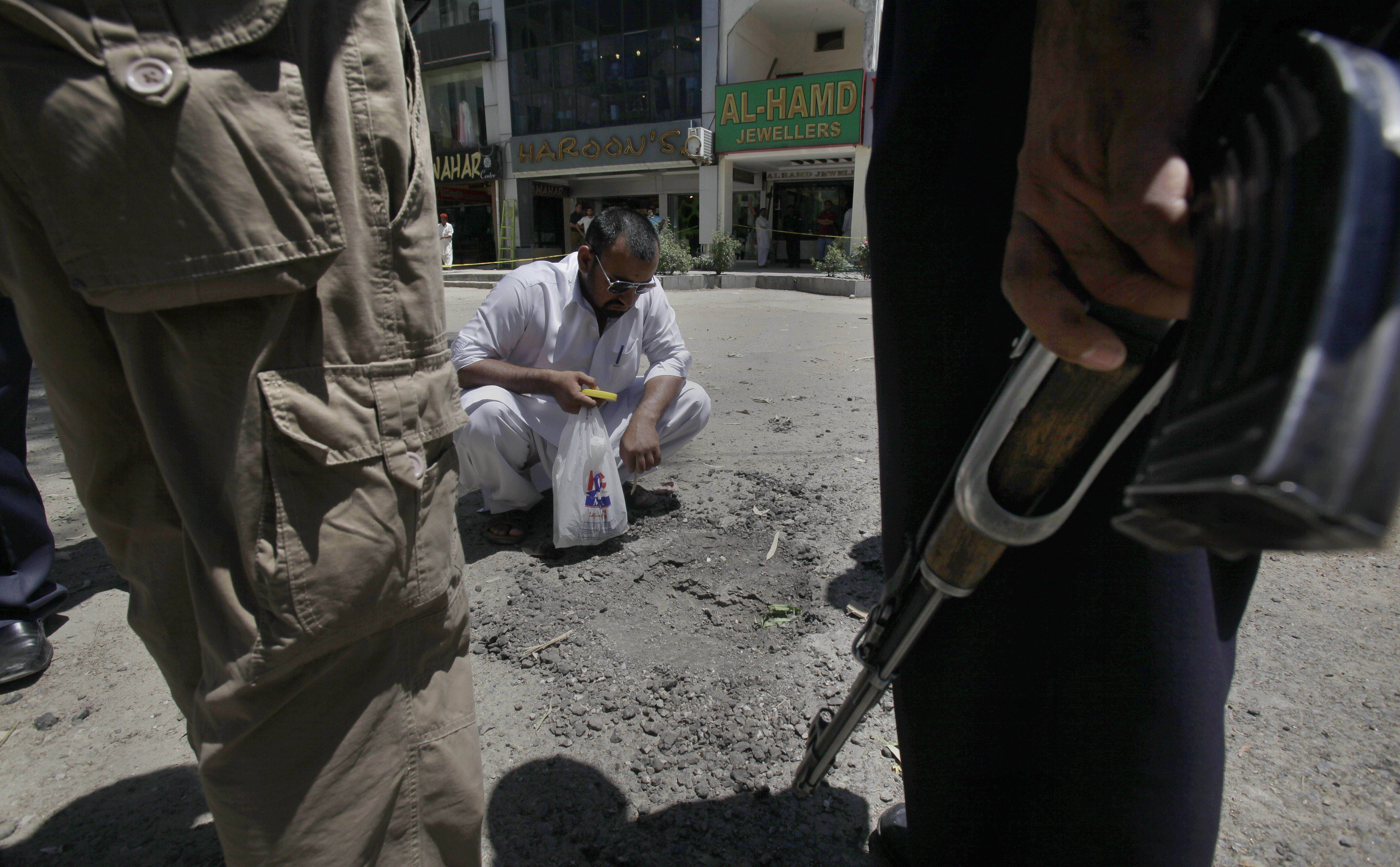 A Pakistani investigator examines a crater caused by a deadly explosion at a market in Islamabad, Pakistan, Saturday, May 24. A bomb exploded in a supermarket parking lot at about 2 a.m. Saturday, killing a guard and wounding a passer-by, police officer Chaudhry Abid said.