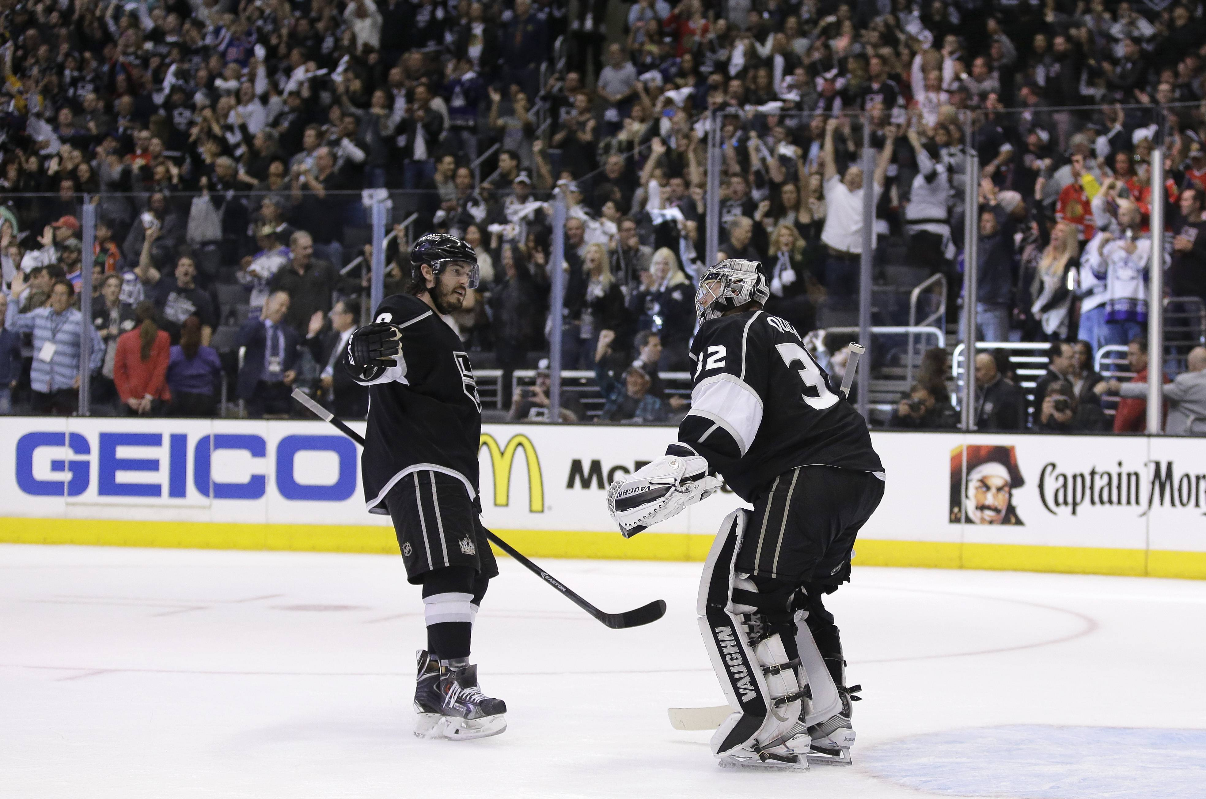 Los Angeles Kings defenseman Drew Doughty, left, celebrates a win against the Chicago Blackhawks with goalie Jonathan Quick after Game 3 of the Western Conference finals of the NHL hockey Stanley Cup playoffs in Los Angeles, Saturday, May 24, 2014.