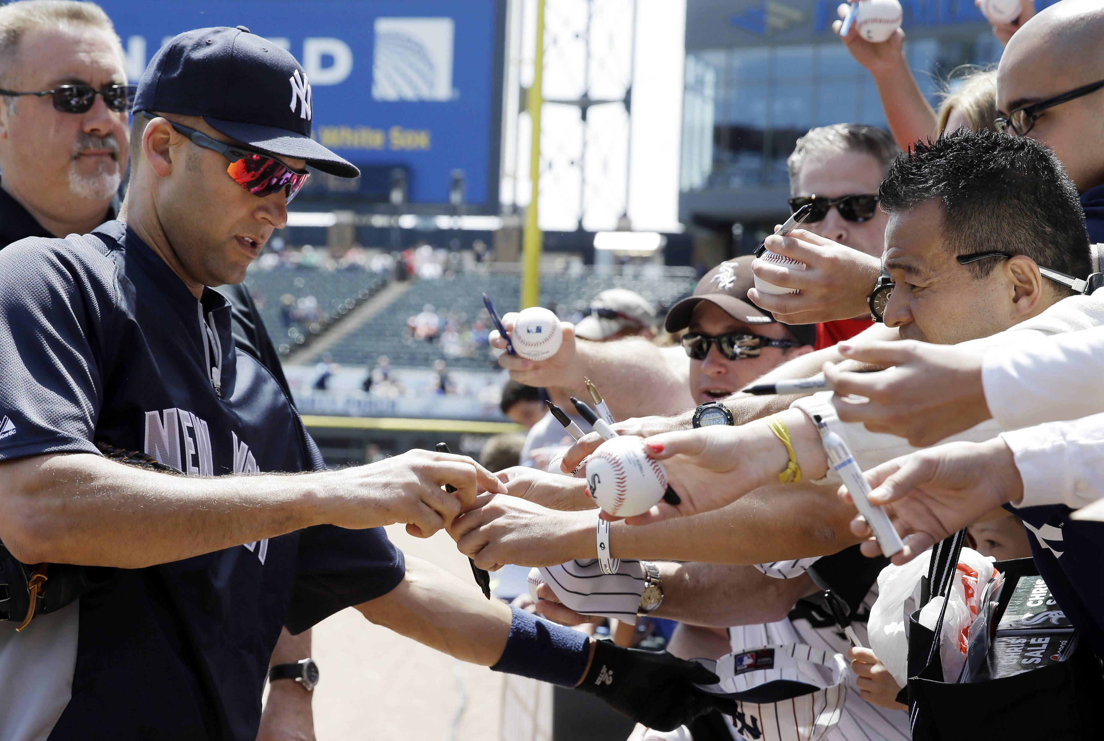 New York Yankees' Derek Jeter, left, signs autographs for fans before a baseball game against the Chicago White Sox in Chicago on Saturday, May 24, 2014.