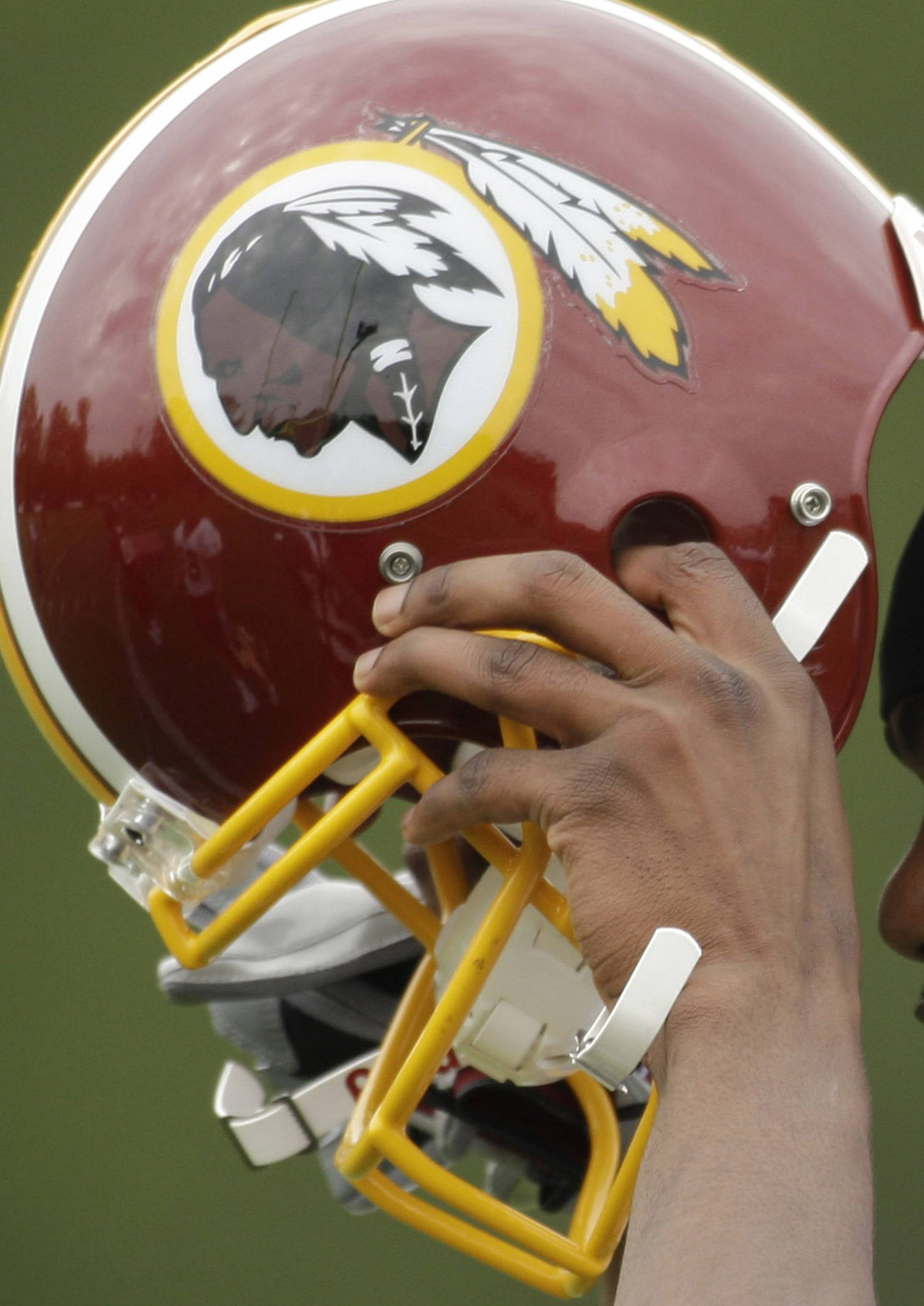 Associated Press/May 1, 2009 Washington Redskin Marko Mitchell puts his helmet on during an NFL football minicamp practice.