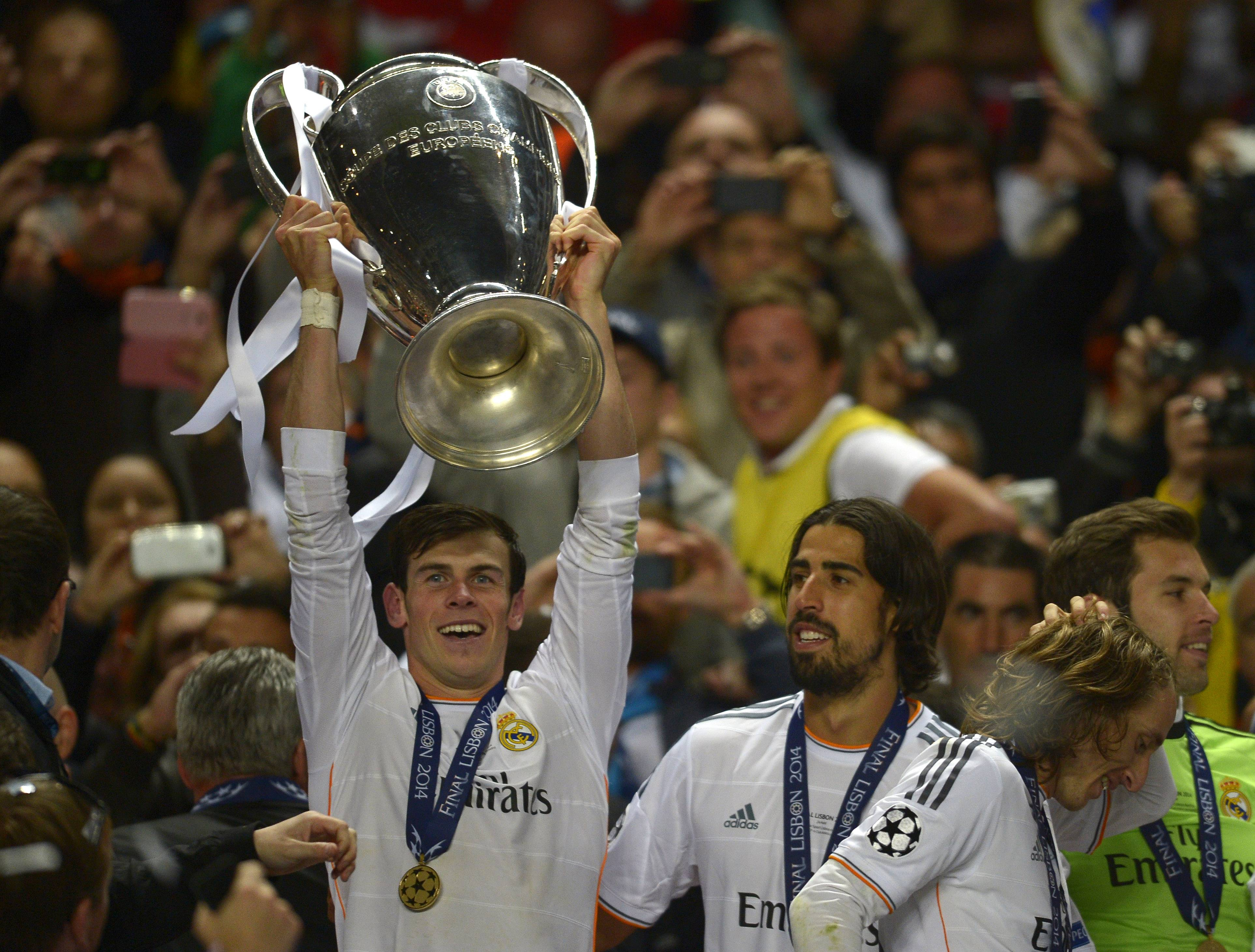 Real's Gareth Bale, lifts the Champion League trophy, after his team won the Champions League final soccer match between Atletico Madrid and Real Madrid in Lisbon, Portugal, Saturday, May 24, 2014.