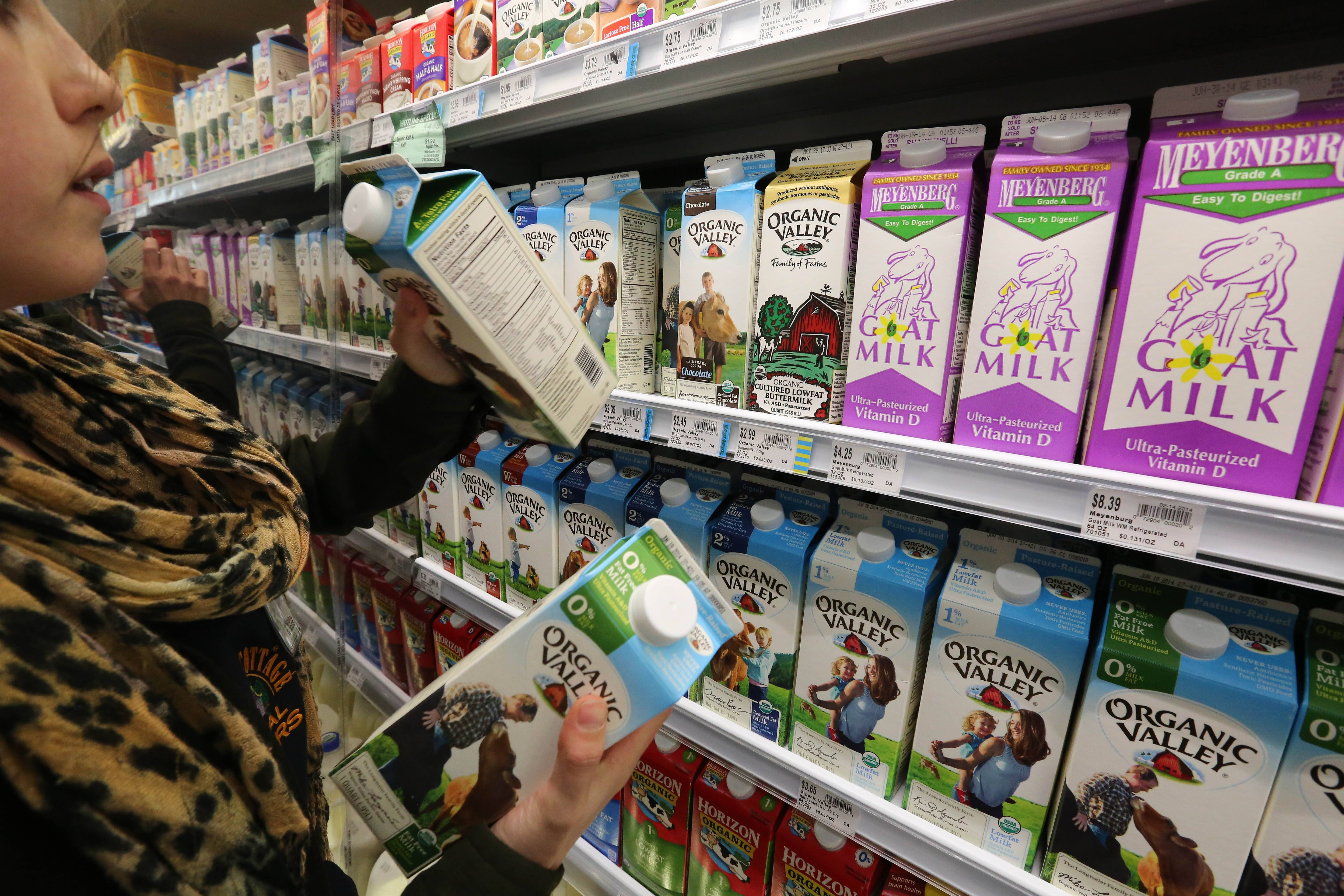 Grocery and dairy assistant Reyna DeLoge stocks dairy products Friday that only use milk from pasture-raised cows, at Vitamin Cottage Natural Grocers, in Denver.