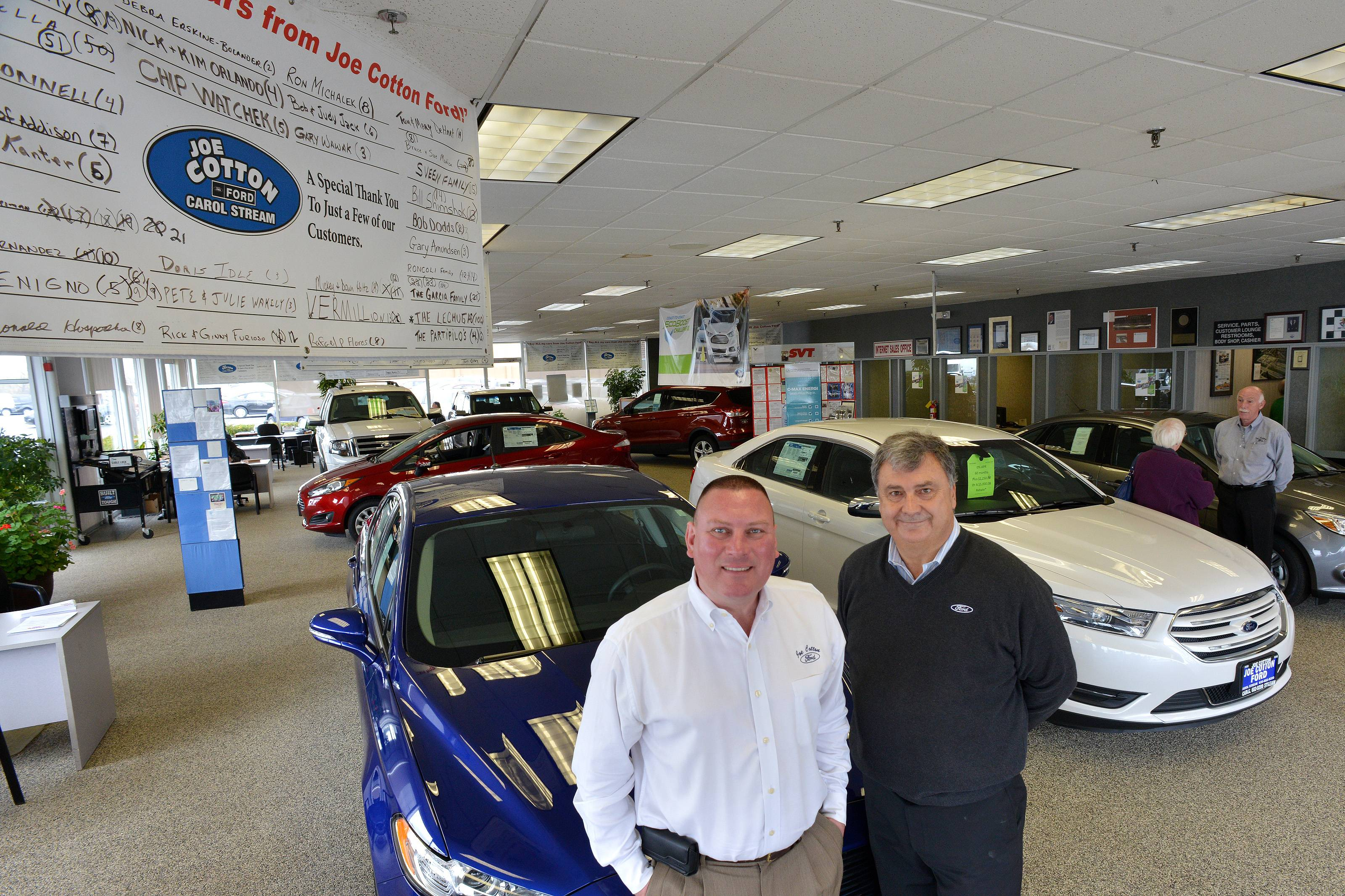 Paul Cotton, right, dealer principle of  Joe Cotton Ford in Carol Stream, works on the showroom floor with Tracy Conn, left, vice president and general manager of the dealership.