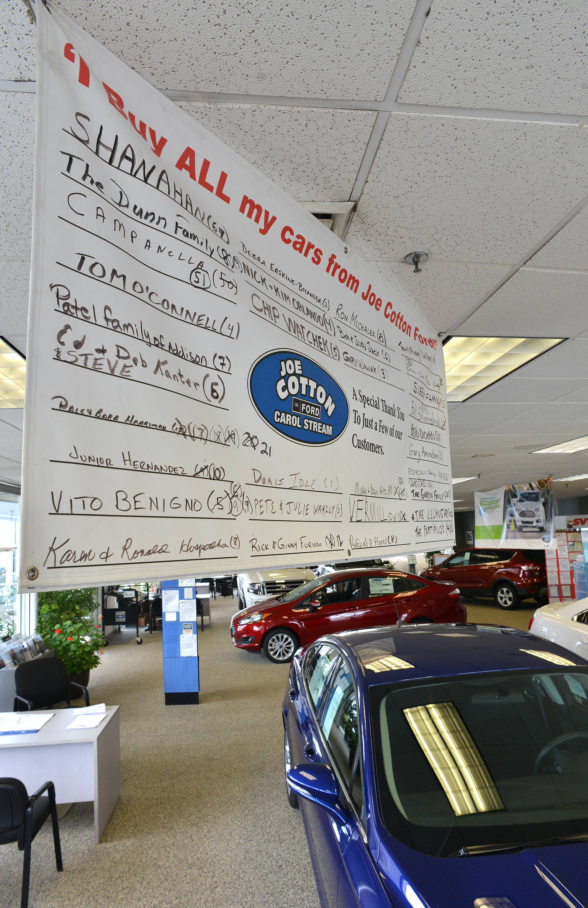 Joe Cotton Ford in Carol Stream honors its repeat customers with banners in the showroom that track how many vehicles they've purchased.