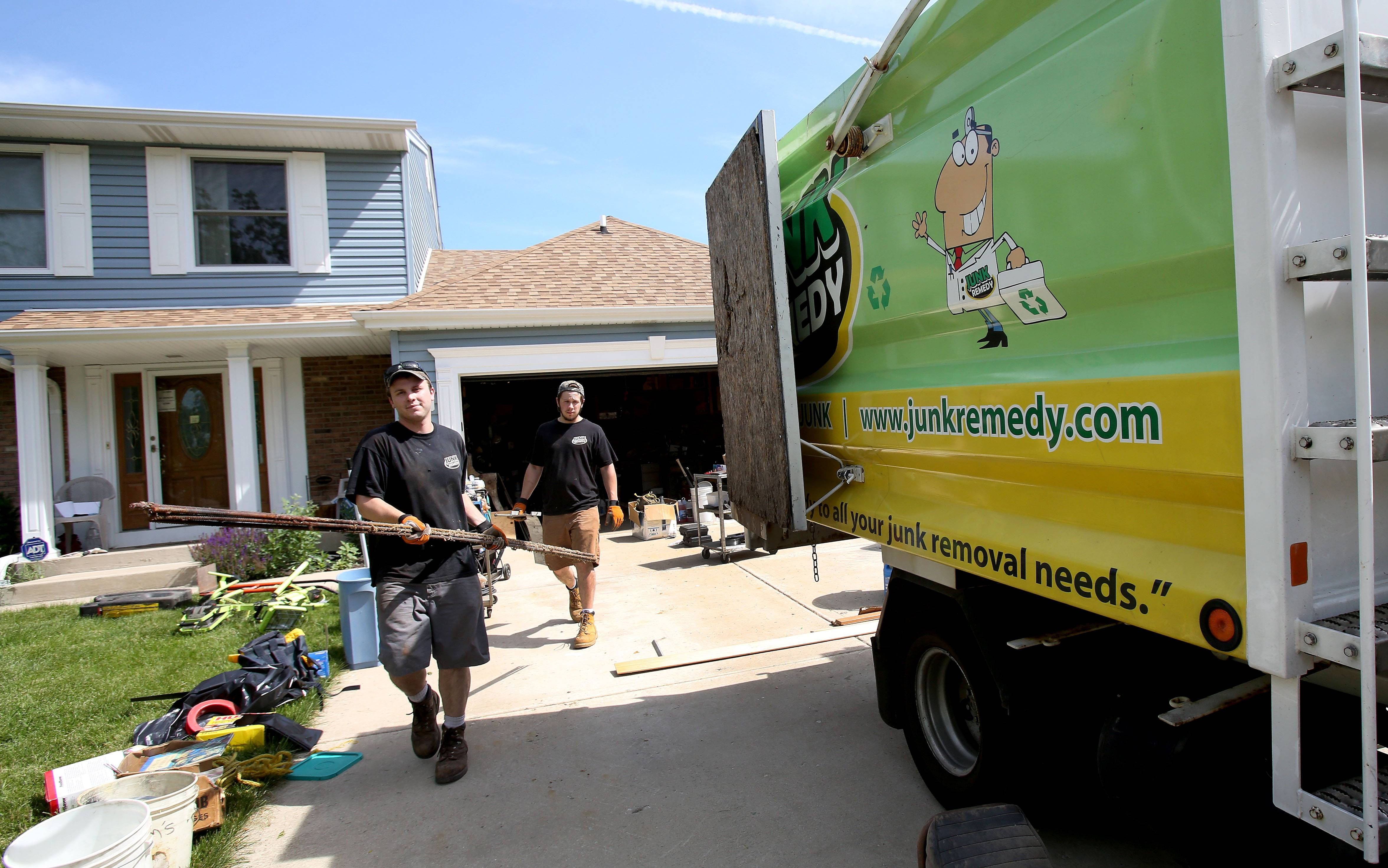 A crew from Junk Remedy cleans out a Roselle homeowner's garage last summer.