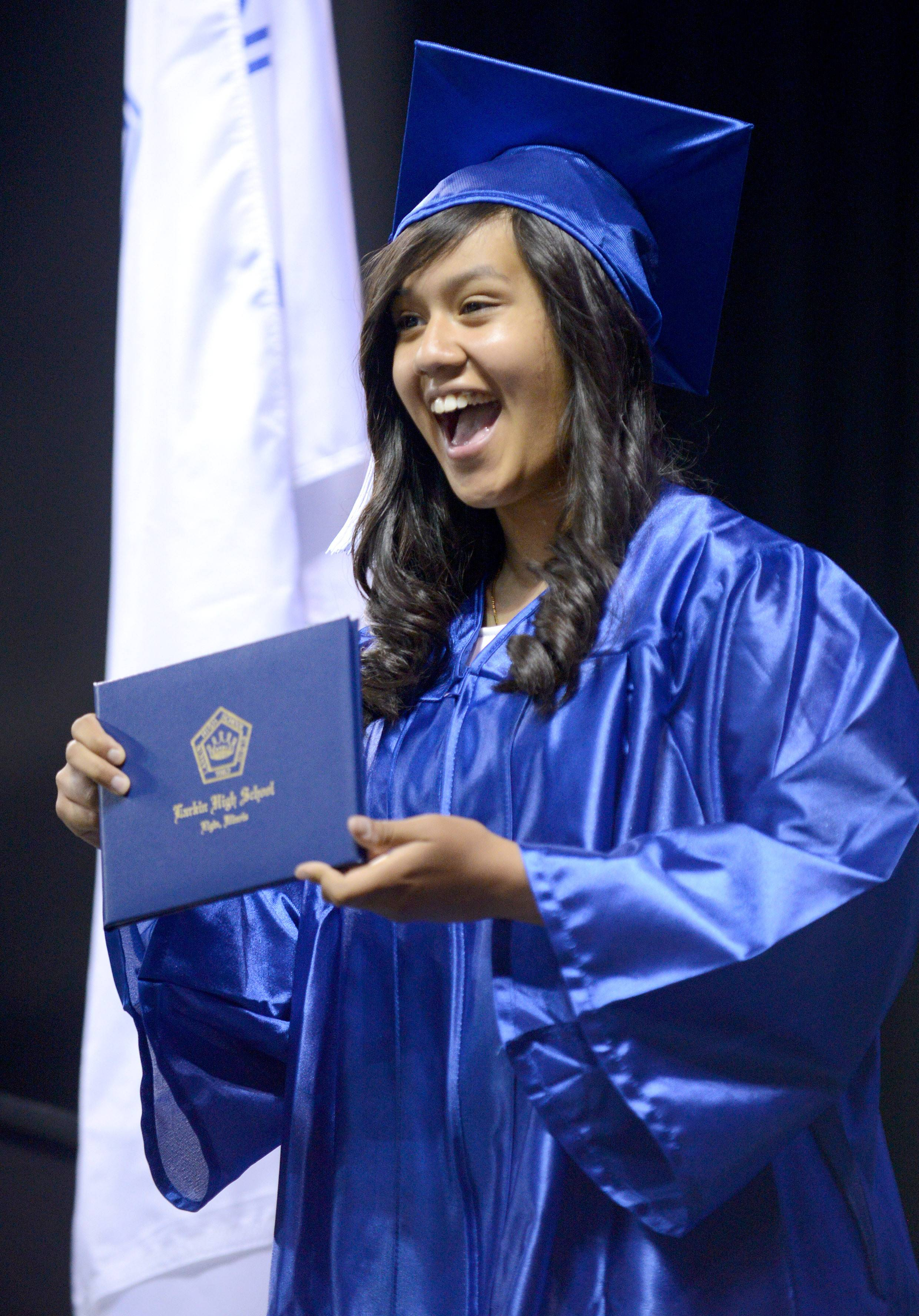 Meryl Hasana of Elgin shows off her diploma to her cheering cousins in the stands at Larkin High School's commencement ceremony at the Sears Centre in Hoffman Estates on Saturday, May 24.
