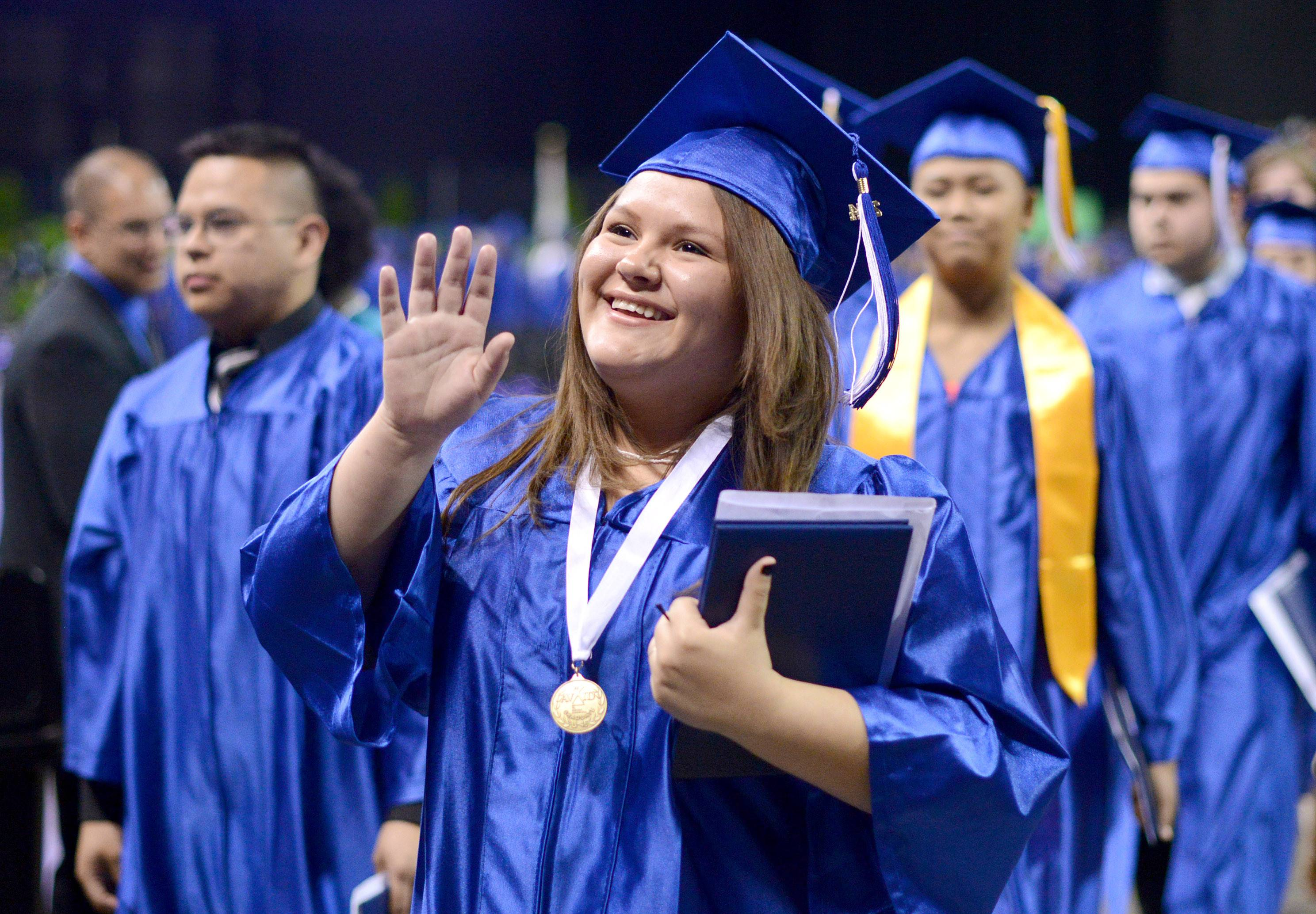 Vanesa Sierra Martinez of Elgin waves to her family in the stands as she exits the floor with diploma in hand at Larkin High School's commencement ceremony at the Sears Centre in Hoffman Estates on Saturday, May 24.