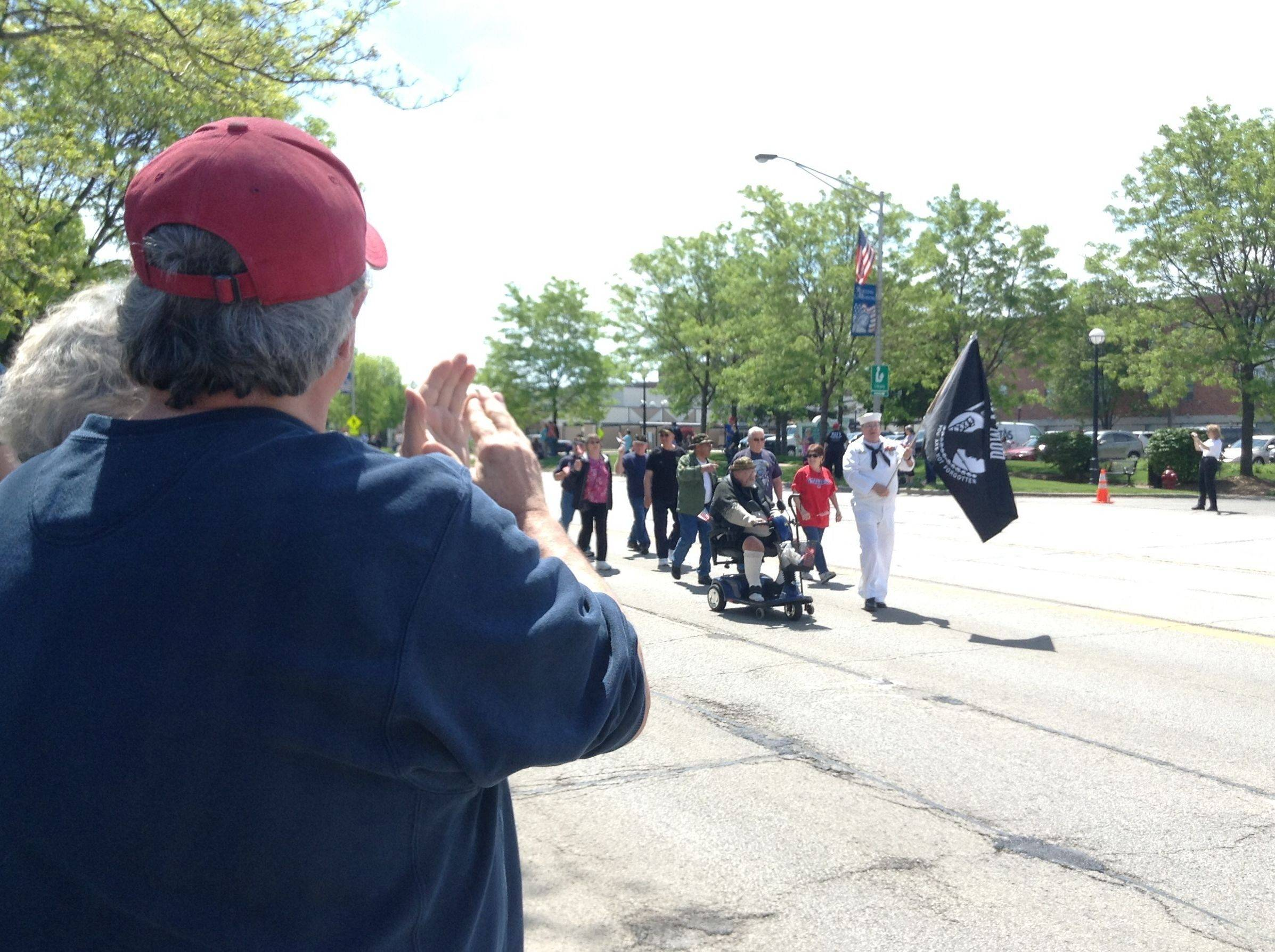 As military veterans march, walk and roll down Kirchoff Road during Saturday's Memorial Day parade in Rolling Meadows, lifelong resident Alan Palmer and his mother, Marjorie, stand and applaud.