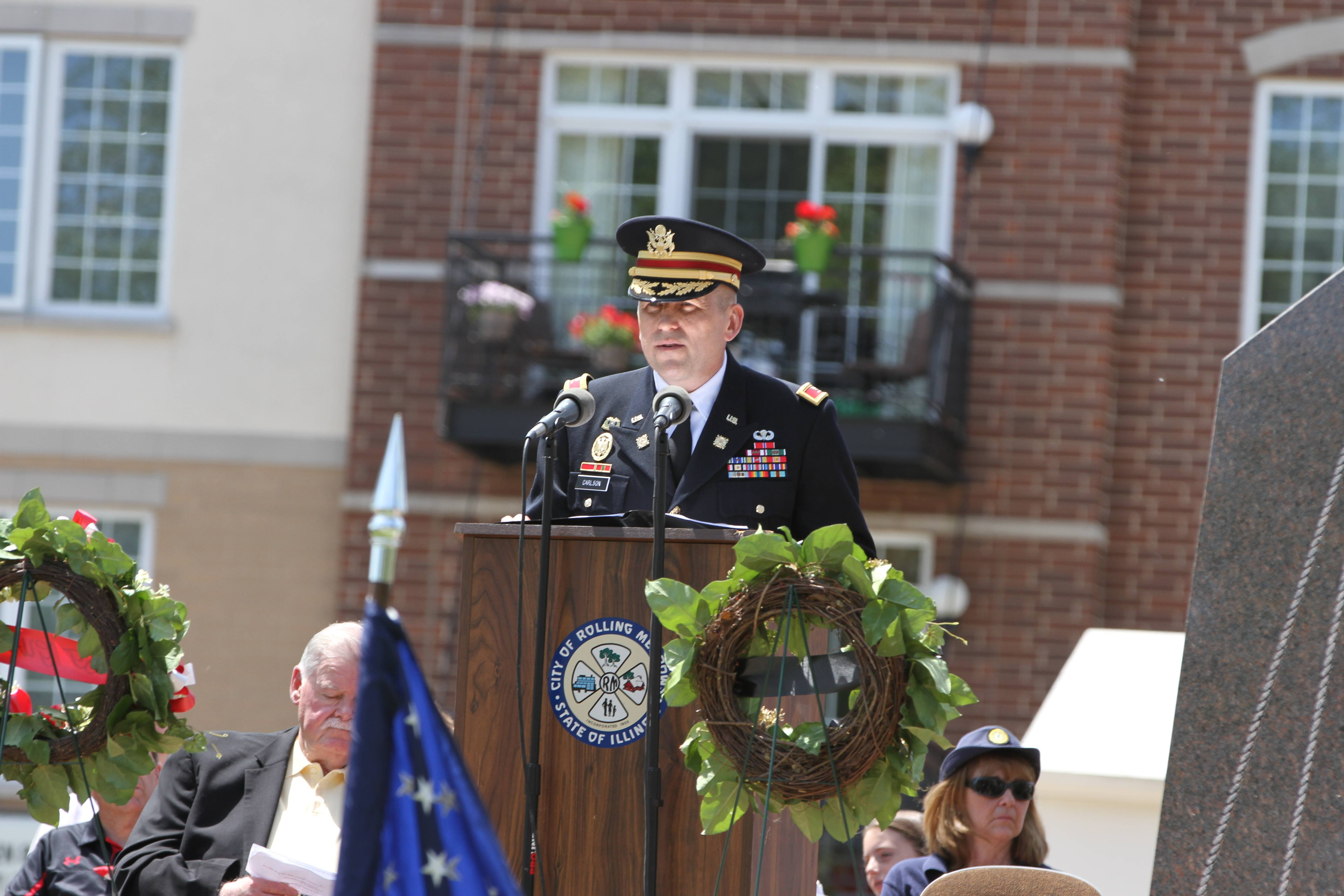 "In his 32nd year of duty, Col. Rob Carlson, commander of the Army Reserve 646th Regional Support Group, tells Saturday's crowd in Rolling Meadows how patriots can remember the day and honor the living by treating Memorial Day as ""a day of reverent celebration."""