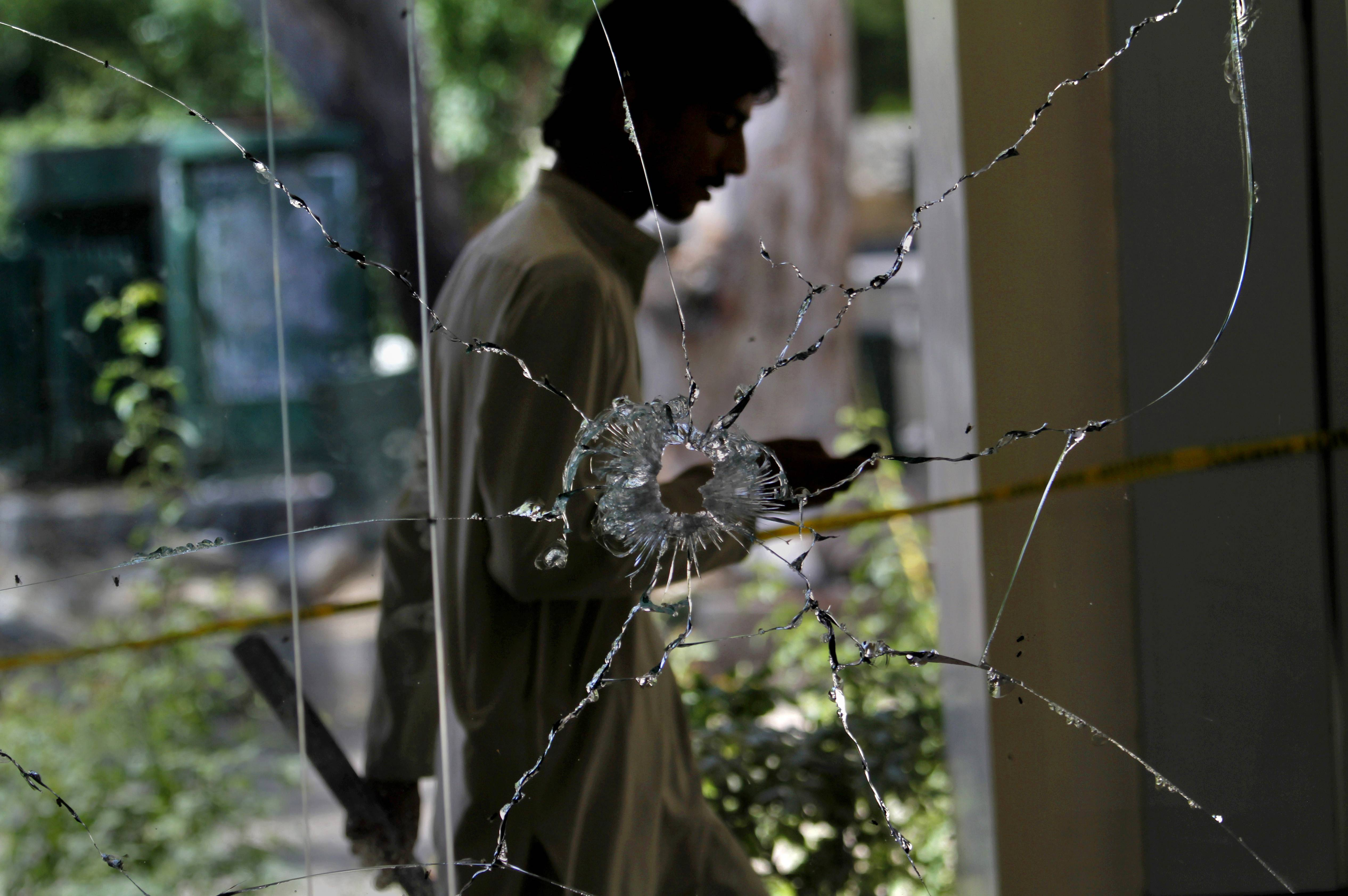 A man walks past a shattered window of shop damaged by a deadly explosion in Islamabad, Pakistan, Saturday, May 24. A bomb exploded in a supermarket parking lot at about 2 a.m. Saturday, killing a guard and wounding a passer-by, police officer Chaudhry Abid said.