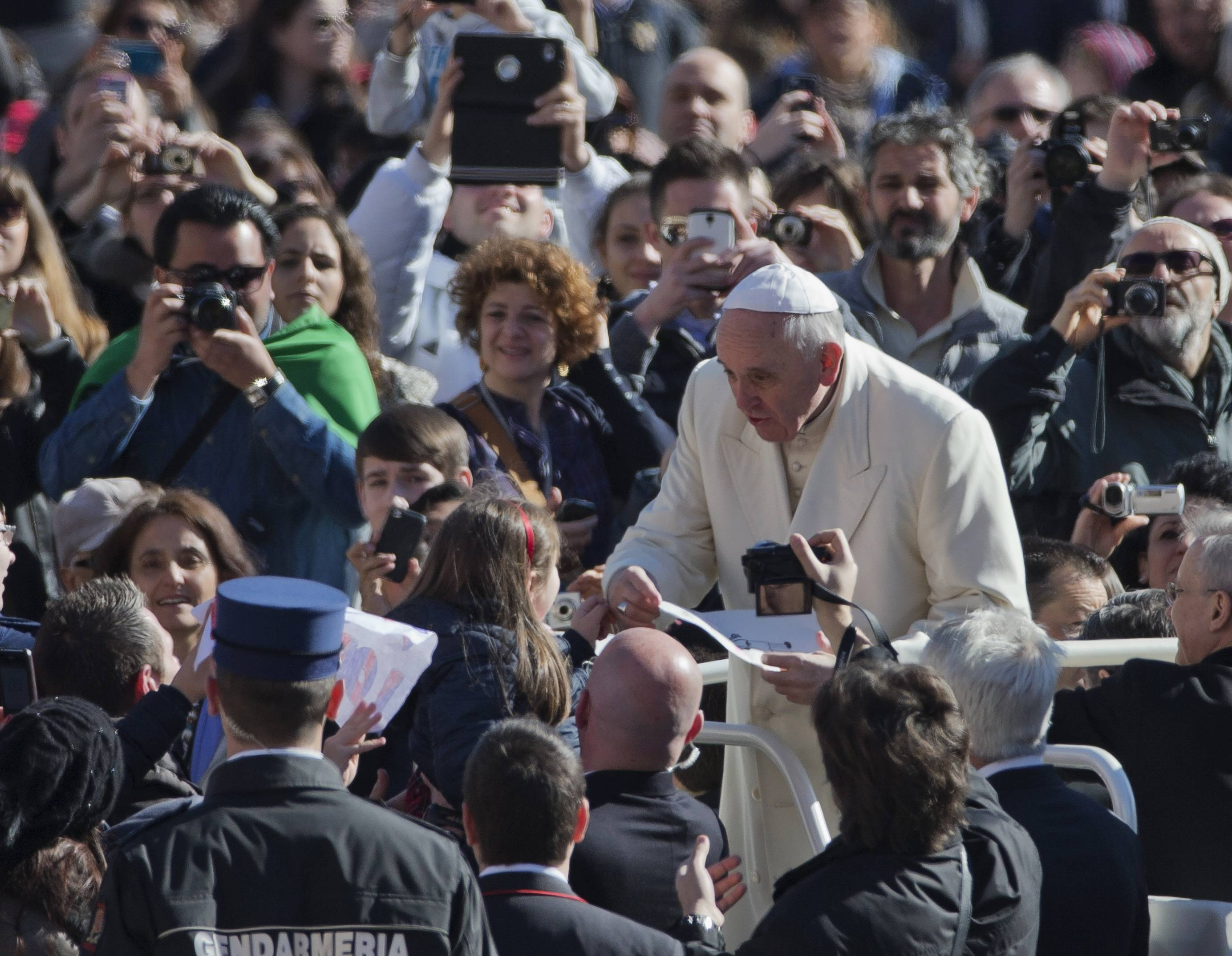 "In this March 5, photo, Pope Francis is presented by a girl with a drawing while touring St. Peter's Square at the Vatican prior to the start of his weekly general audience. Pope Francis insists his weekend pilgrimage to the Middle East is a ""strictly religious"" commemoration of a key turning point in Catholic-Orthodox relations. But the three-day mission is the most delicate of his papacy and will test his diplomatic chops as he negotiates Israeli-Palestinian tensions and fallout from Syria's civil war."