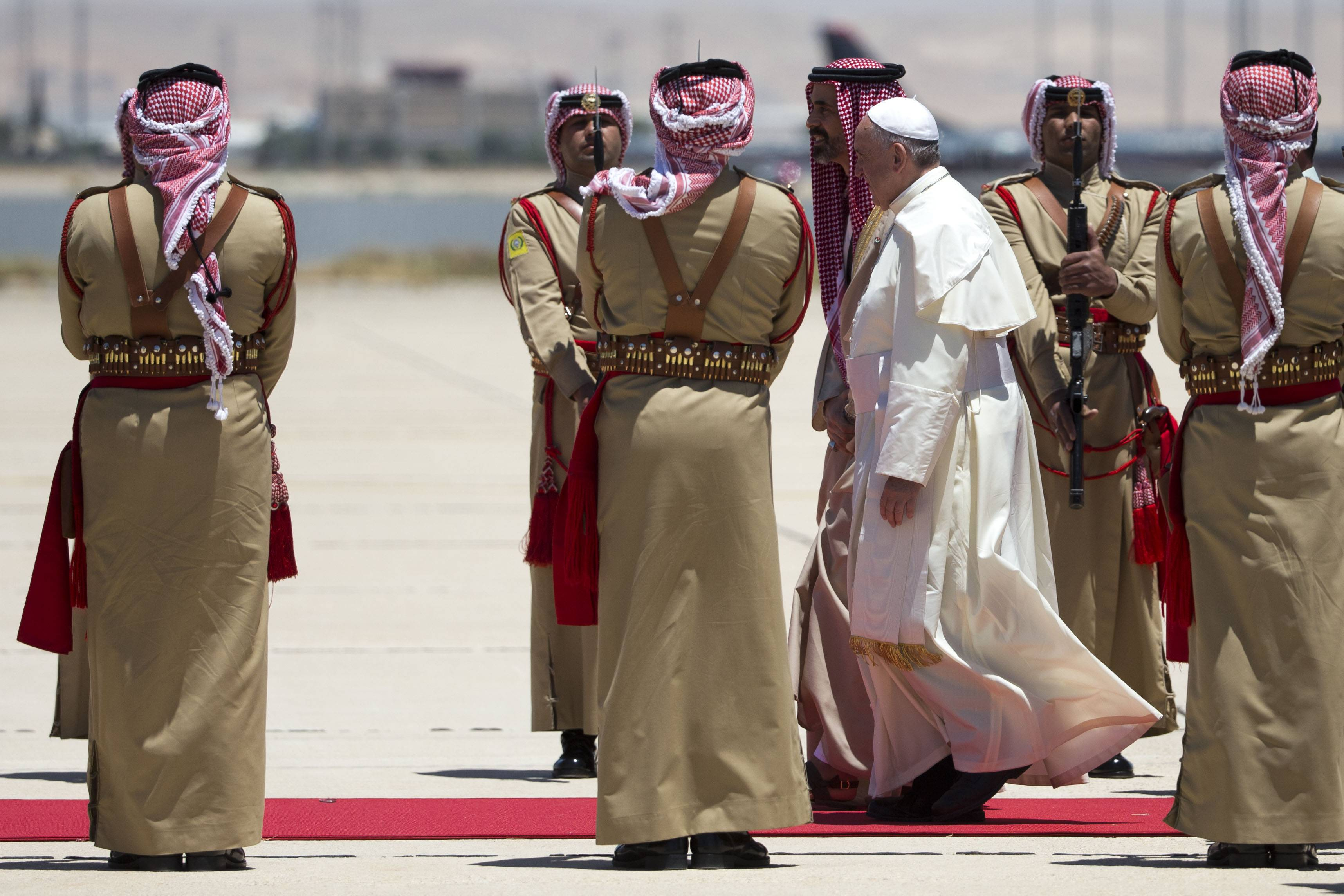 Pope Francis is flanked by a royal house representatives upon his arrival at Amman's airport, Jordan, Saturday, May 24. The pontiff is in Jordan on the first of a three day trip to the Middle East that will also take him to the West Bank and Israel.