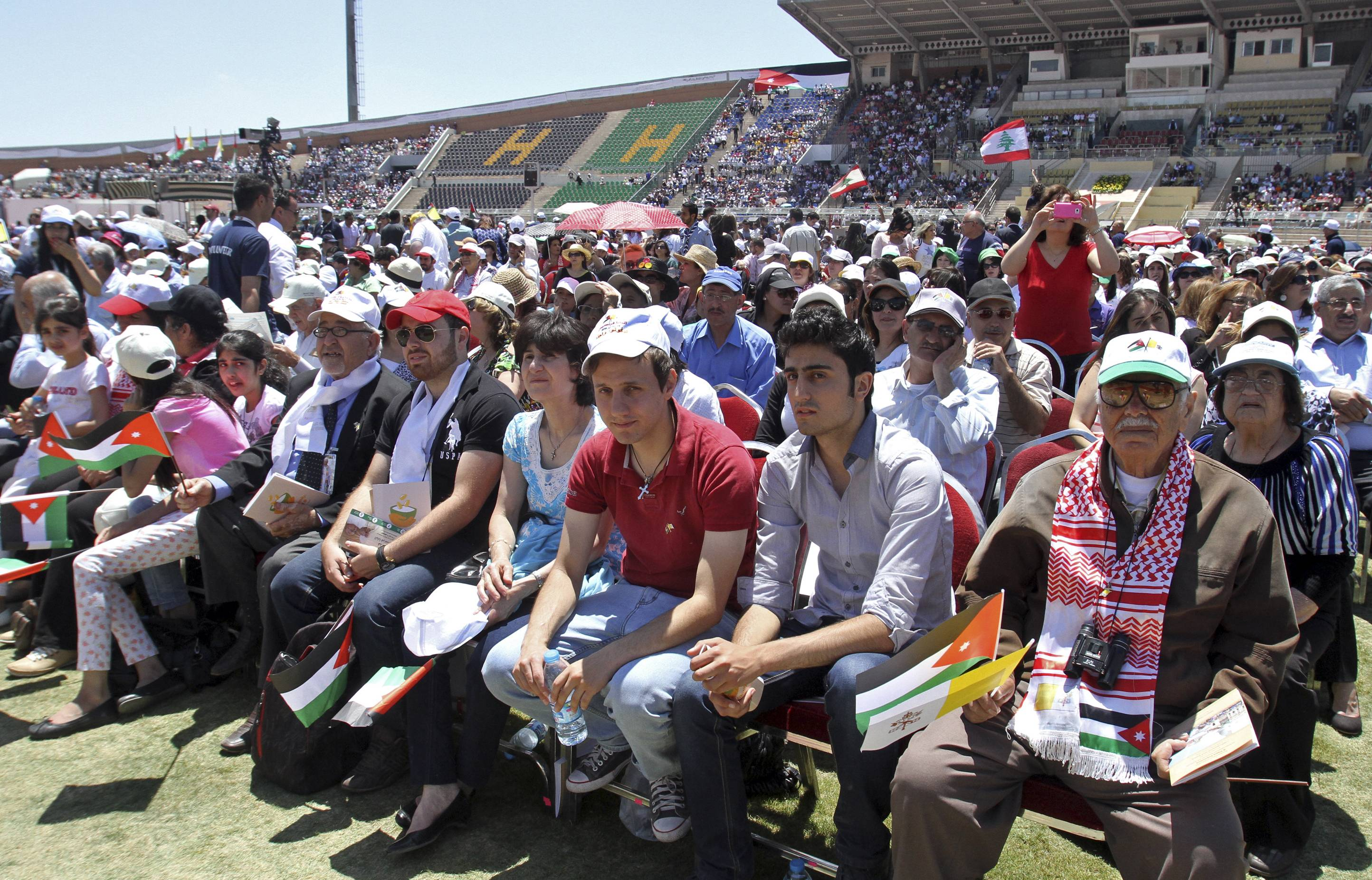 Jordanians and Christians from various nationalities and denominations hold Vatican and national flags as they congregate at Amman's International Stadium waiting for the arrival of Pope Francis where he will conduct a mass prayer, in Amman, Jordan, Saturday, May 24.