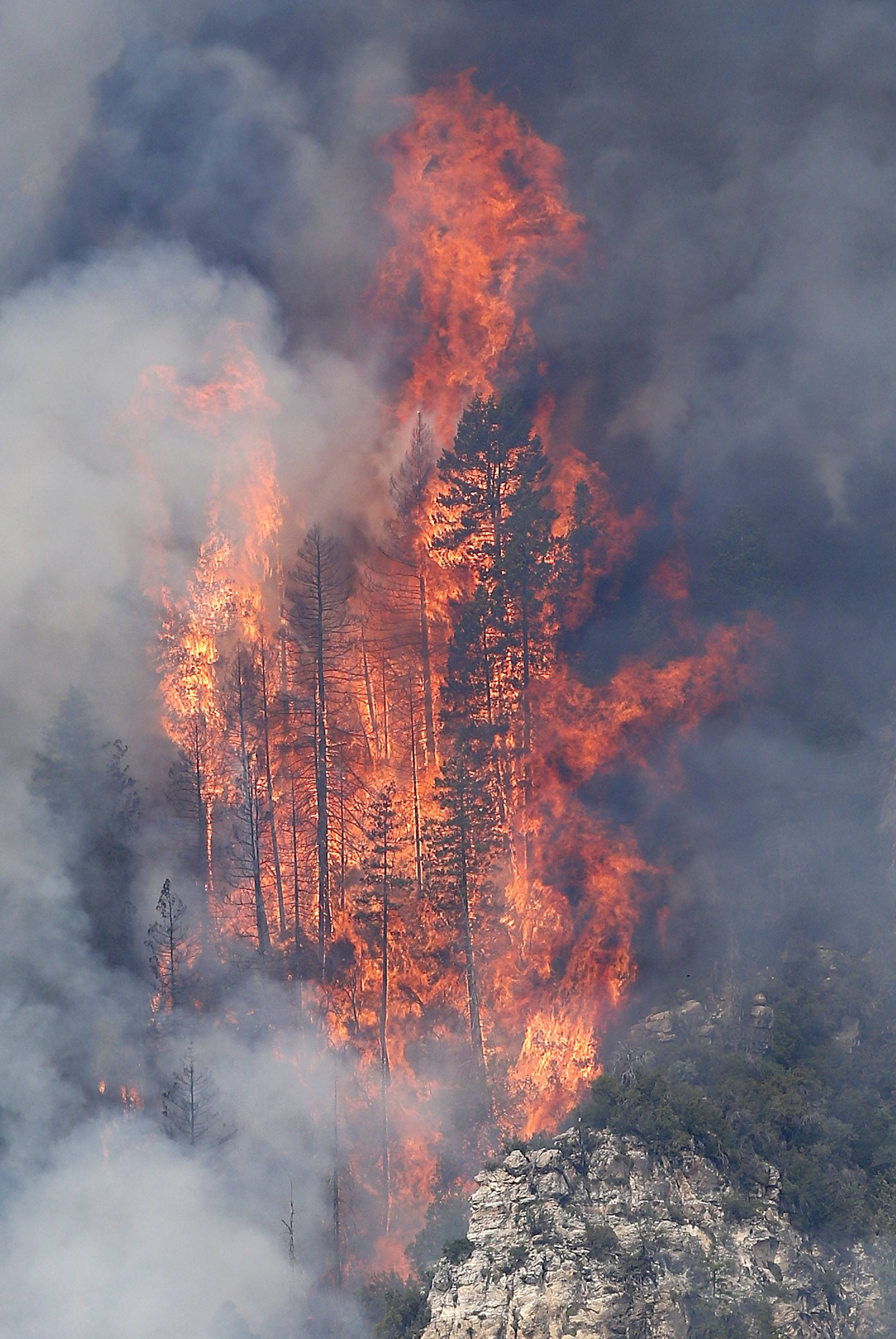 Flames shoot up over 125-feet high as the Slide Fire burns up Oak Creek Canyon on Friday, May 23, near Flagstaff, Ariz. The fire has burned approximately 7,500 acres and is five percent contained.