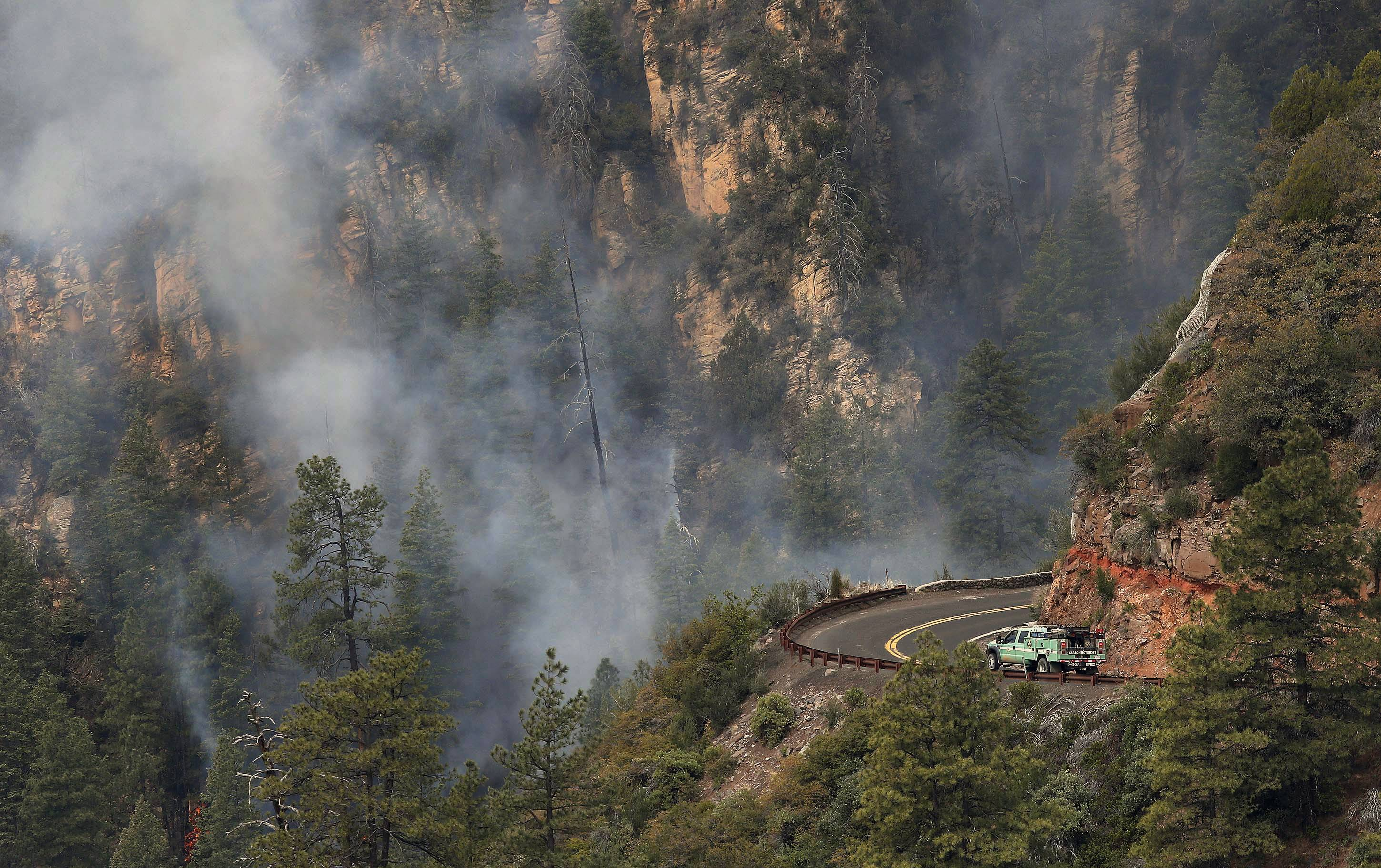 A truck drives along a road near the Slide Fire as it burns up Oak Creek Canyon nearby on Friday, May 23, near Flagstaff, Ariz. The fire has burned approximately 7,500 acres.