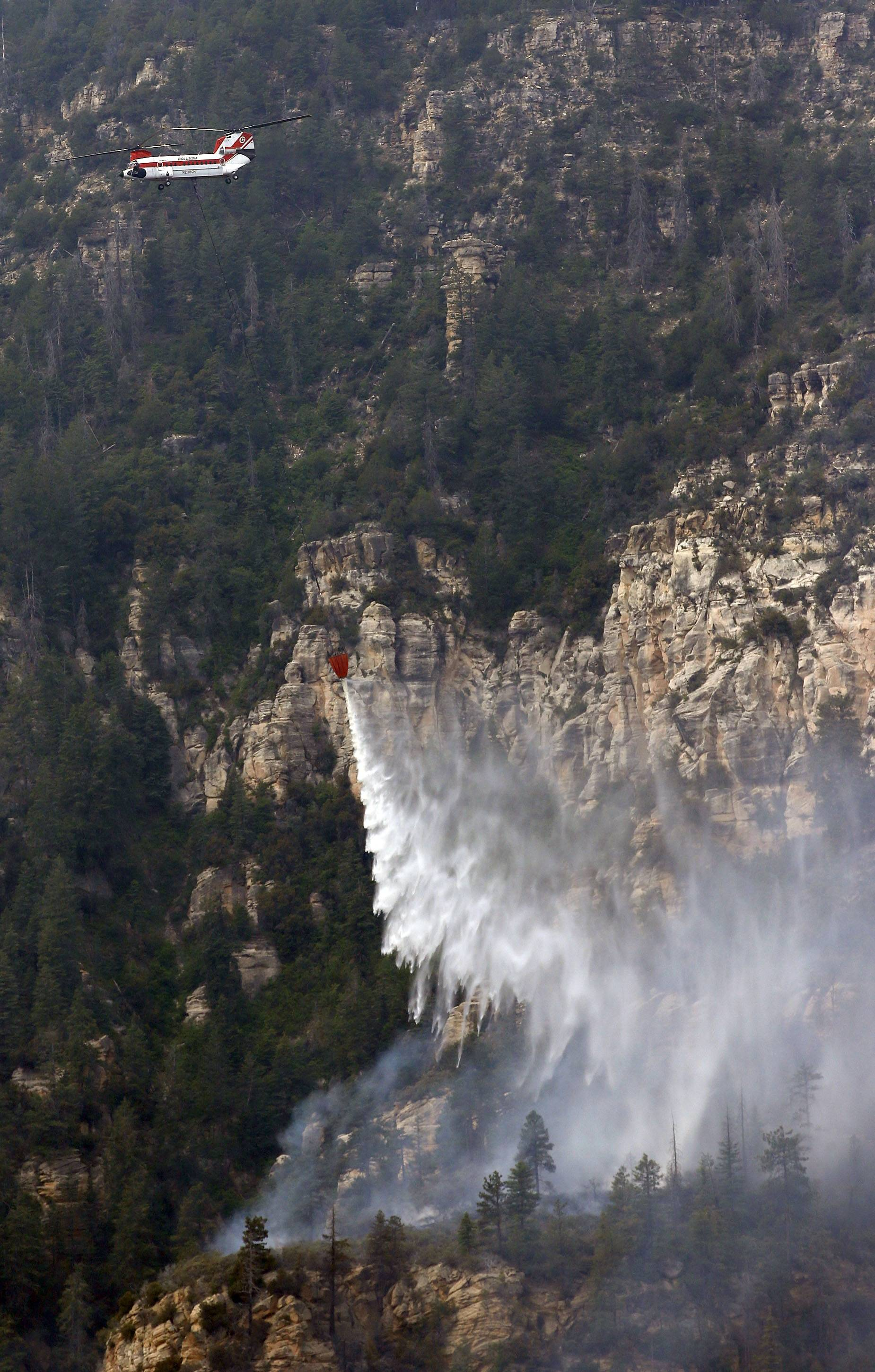 A Heavy Type-1 Vertol Helictoper dumps 2,800 gallons of water onto the Slide Fire as it burns up Oak Creek Canyon on Friday, May 23, near Flagstaff, Ariz. The fire has burned approximately 7,500 acres and is five percent contained.