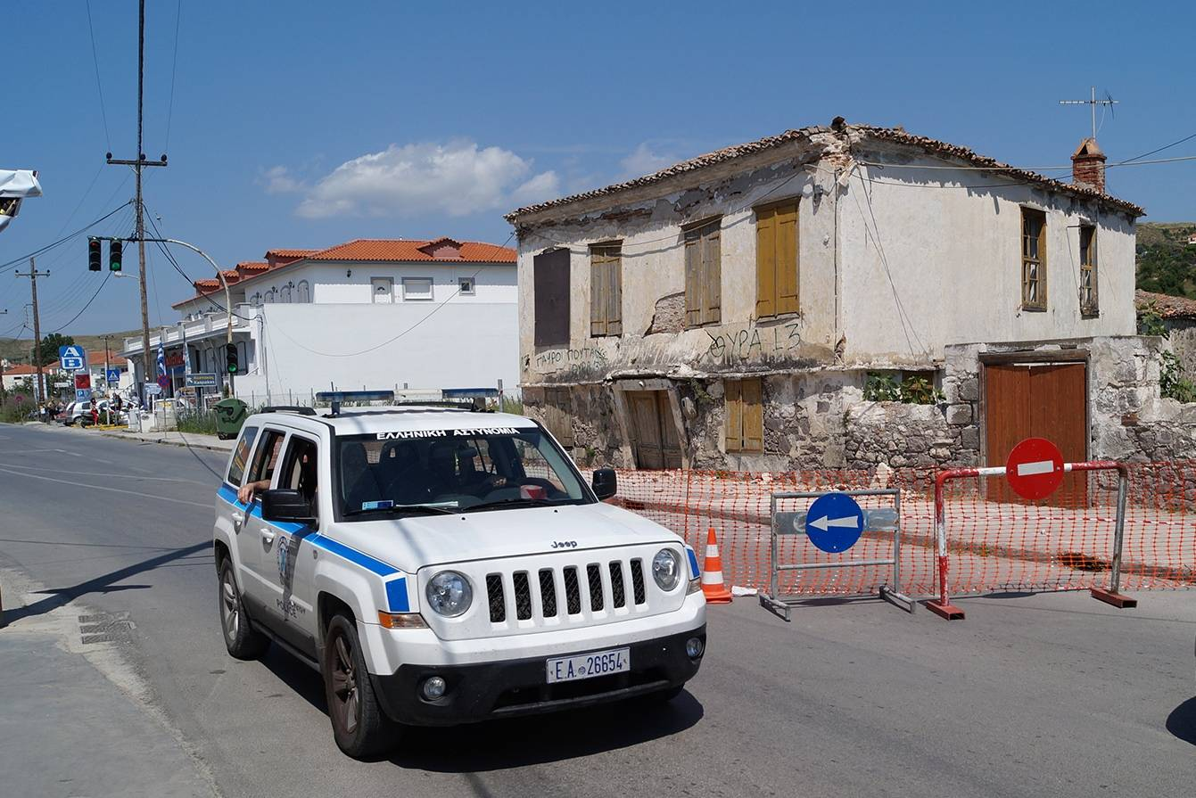 Police patrol past a damaged building Saturday after a magnitude 6.3 earthquake on the northeastern Aegean Sea island of Lemnos, Greece.