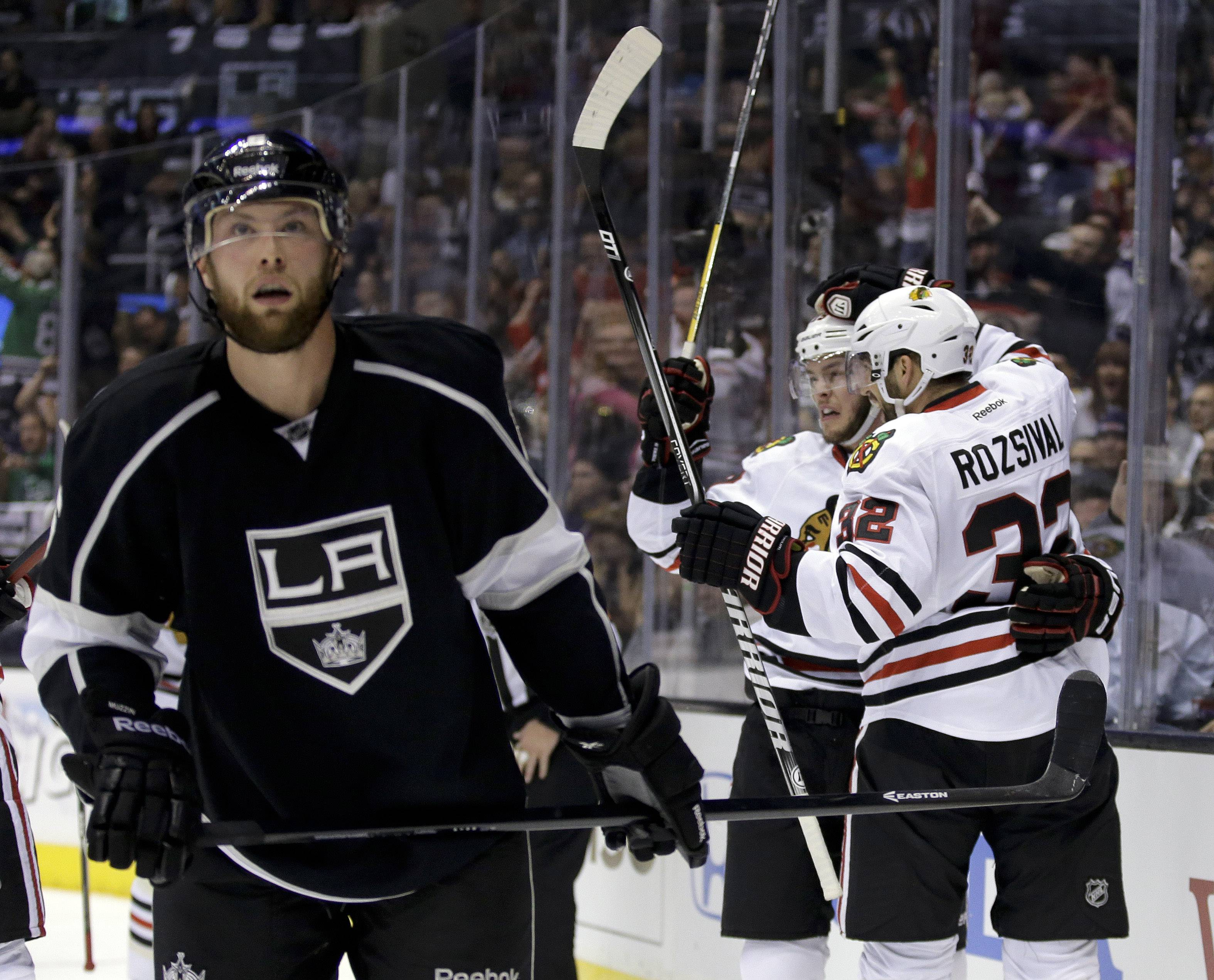 Chicago Blackhawks center Jonathan Toews, center, celebrates his goal with teammate Michal Rozsival, right, as Los Angeles Kings defenseman Jake Muzzin skates off during the first period of Game 3 of the Western Conference finals of the NHL hockey Stanley Cup playoffs in Los Angeles, Saturday, May 24, 2014.