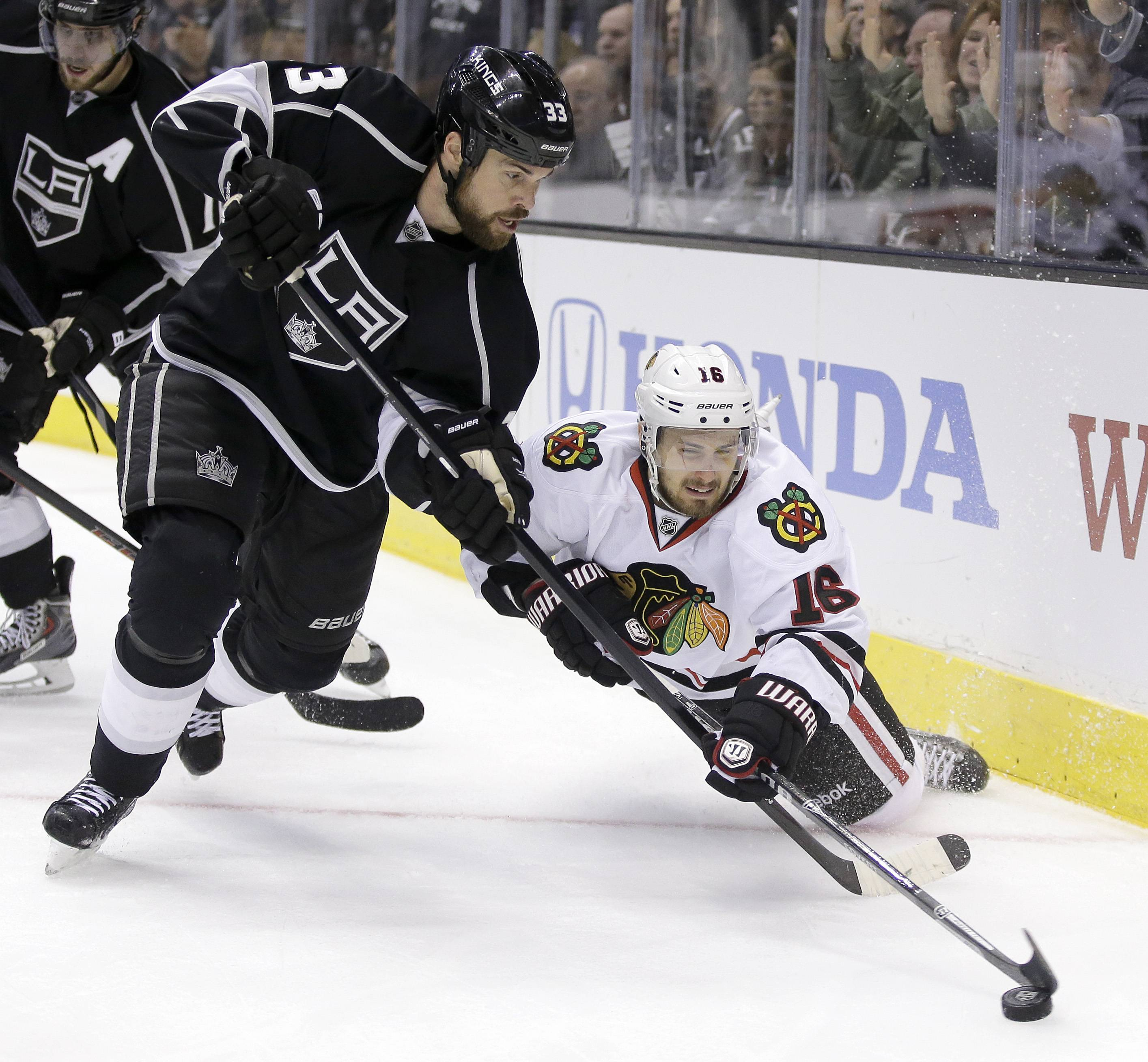 Los Angeles Kings defenseman Willie Mitchell, left, steals the puck from Chicago Blackhawks center Marcus Kruger during the third period of Game 3 of the Western Conference finals of the NHL hockey Stanley Cup playoffs in Los Angeles, Saturday, May 24, 2014.