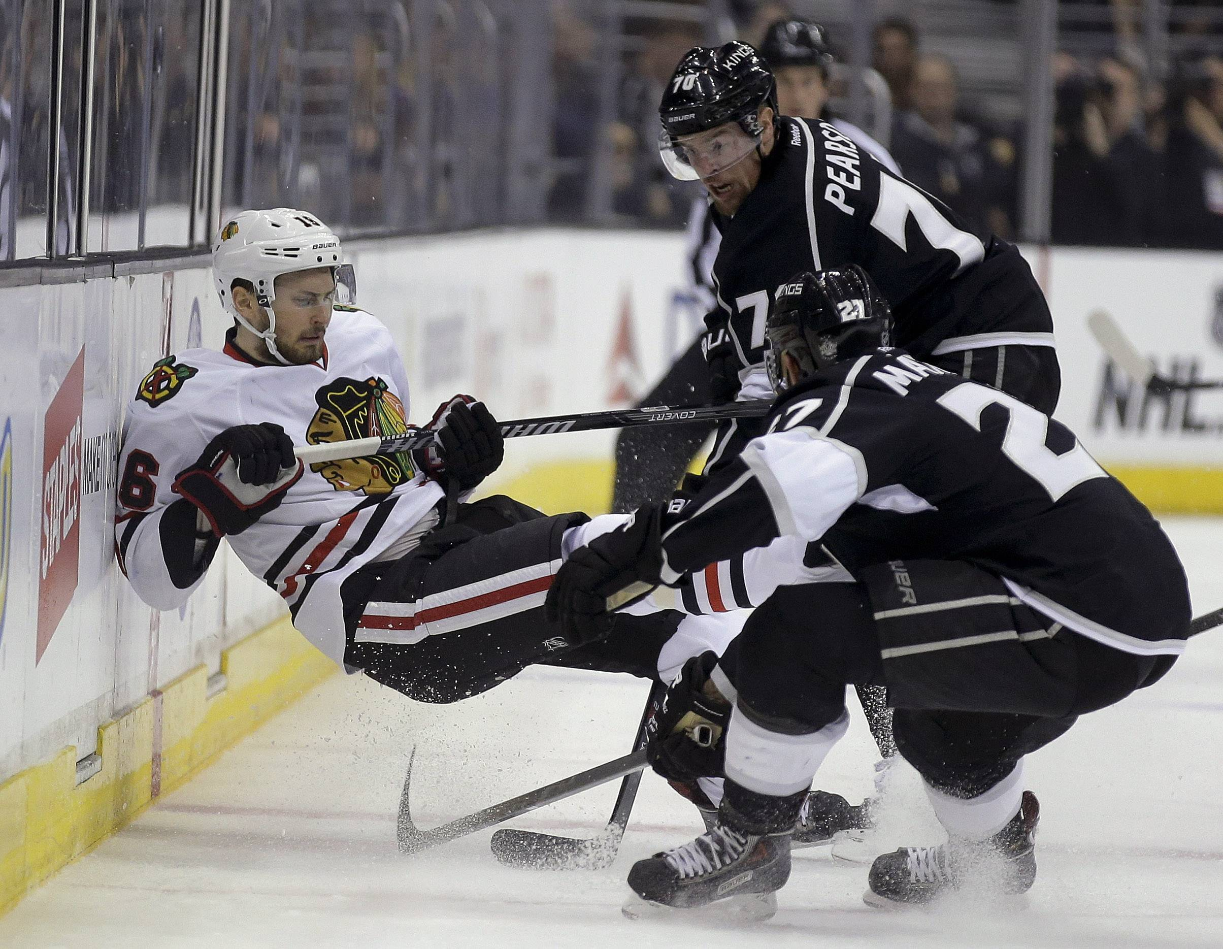 Chicago Blackhawks center Marcus Kruger, left, is checked by Los Angeles Kings defenseman Alec Martinez, and left wing Tanner Pearson, top, during the first period of Game 3 of the Western Conference finals of the NHL hockey Stanley Cup playoffs in Los Angeles, Saturday, May 24, 2014.