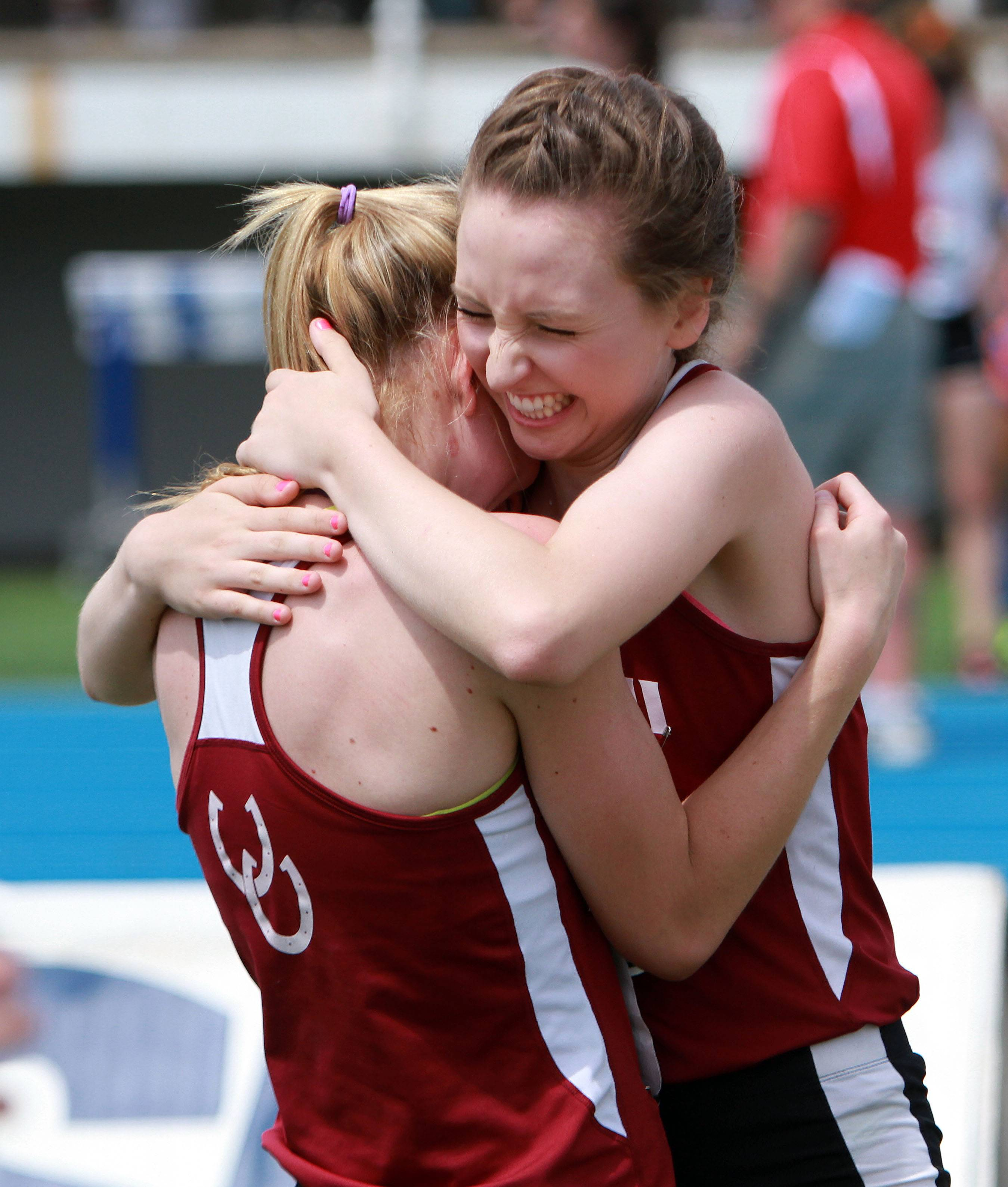 Montini's Emma Makowski, right, hugs Gianna Salzbrunn after a good finish in the 4x800-meter relay during the girls track and field state finals at Eastern Illinois University in Charleston Saturday.