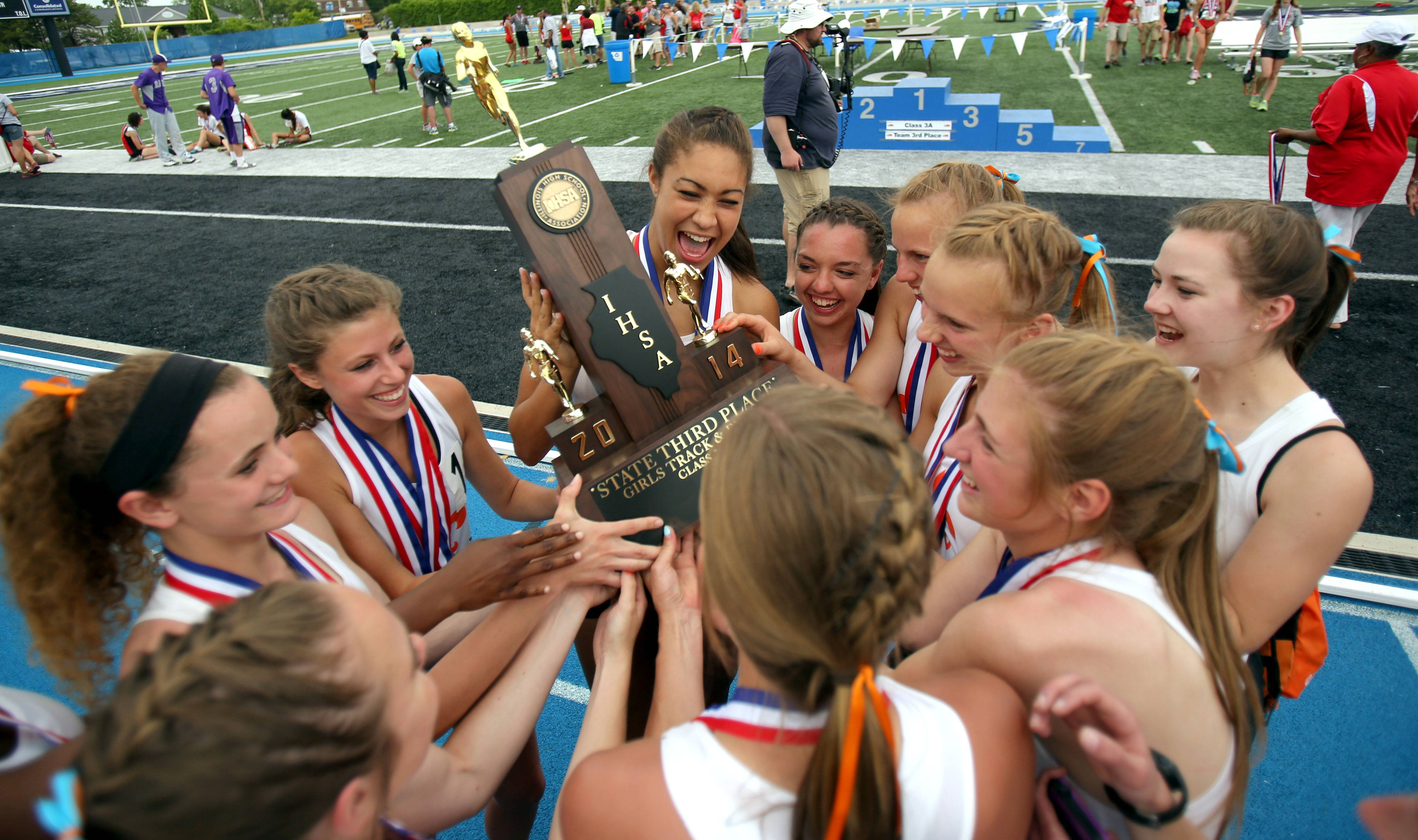 St. Charles East teammates celebrate around the Class 3A 3rd place trophy during the girls track and field state finals at Eastern Illinois University in Charleston Saturday.