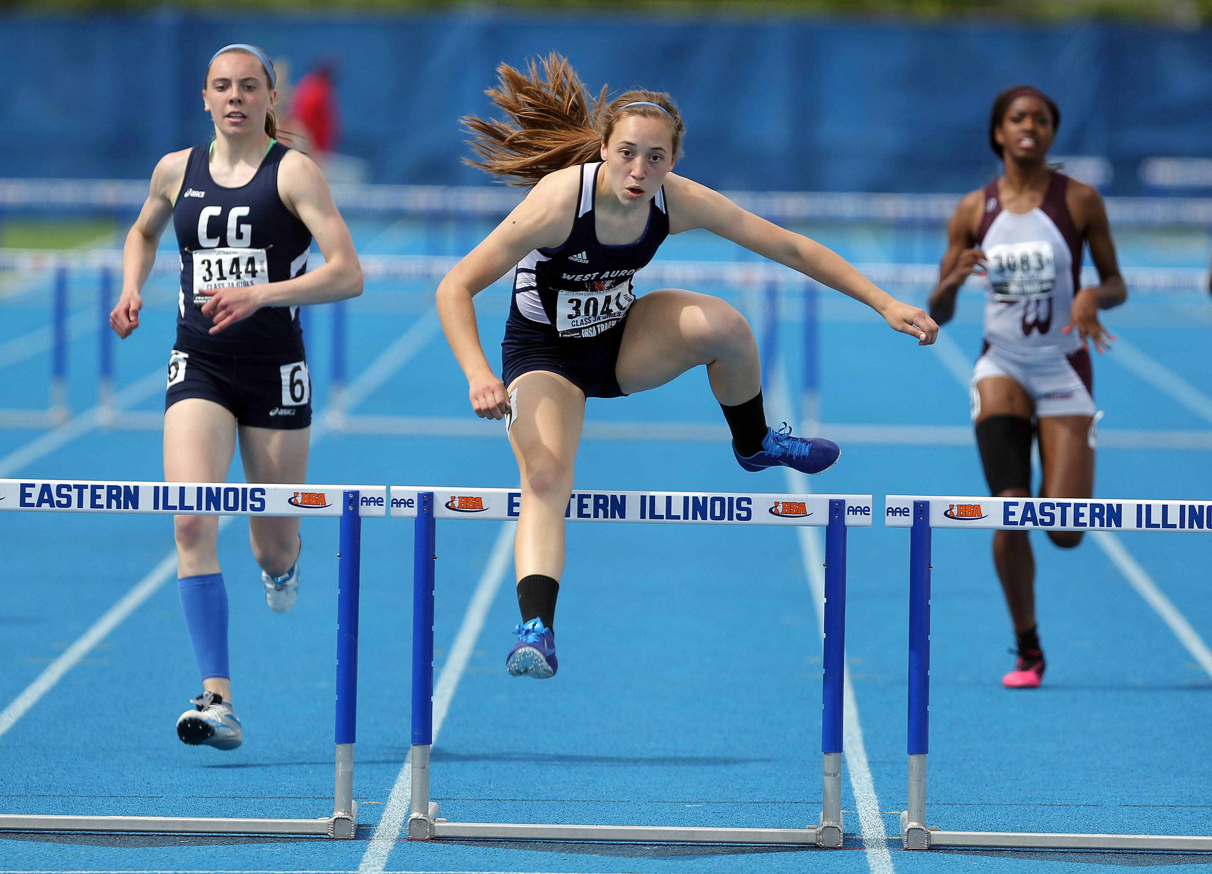 West Aurora's Emma Spagnola, center, clears the final hurdle in the class 3A 300-meter low hurdles during the girls track and field state finals at Eastern Illinois University in Charleston Saturday.
