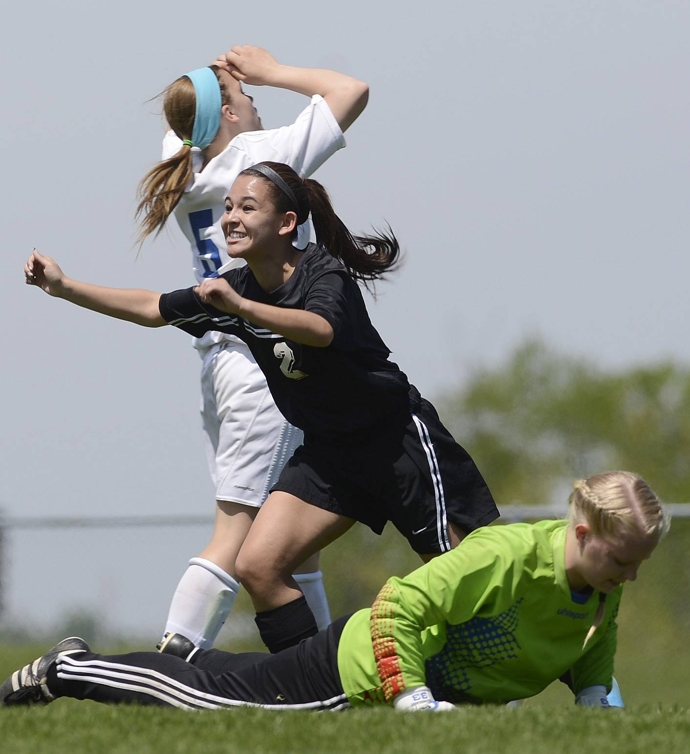 Larissa Dooley of Prairie Ridge runs to celebrate her first-half goal with teammates as goalkeeper Kara Jones, bottom, and Alyssa Brey of Lakes react during the Class 2A regional final at Lakes on Saturday.