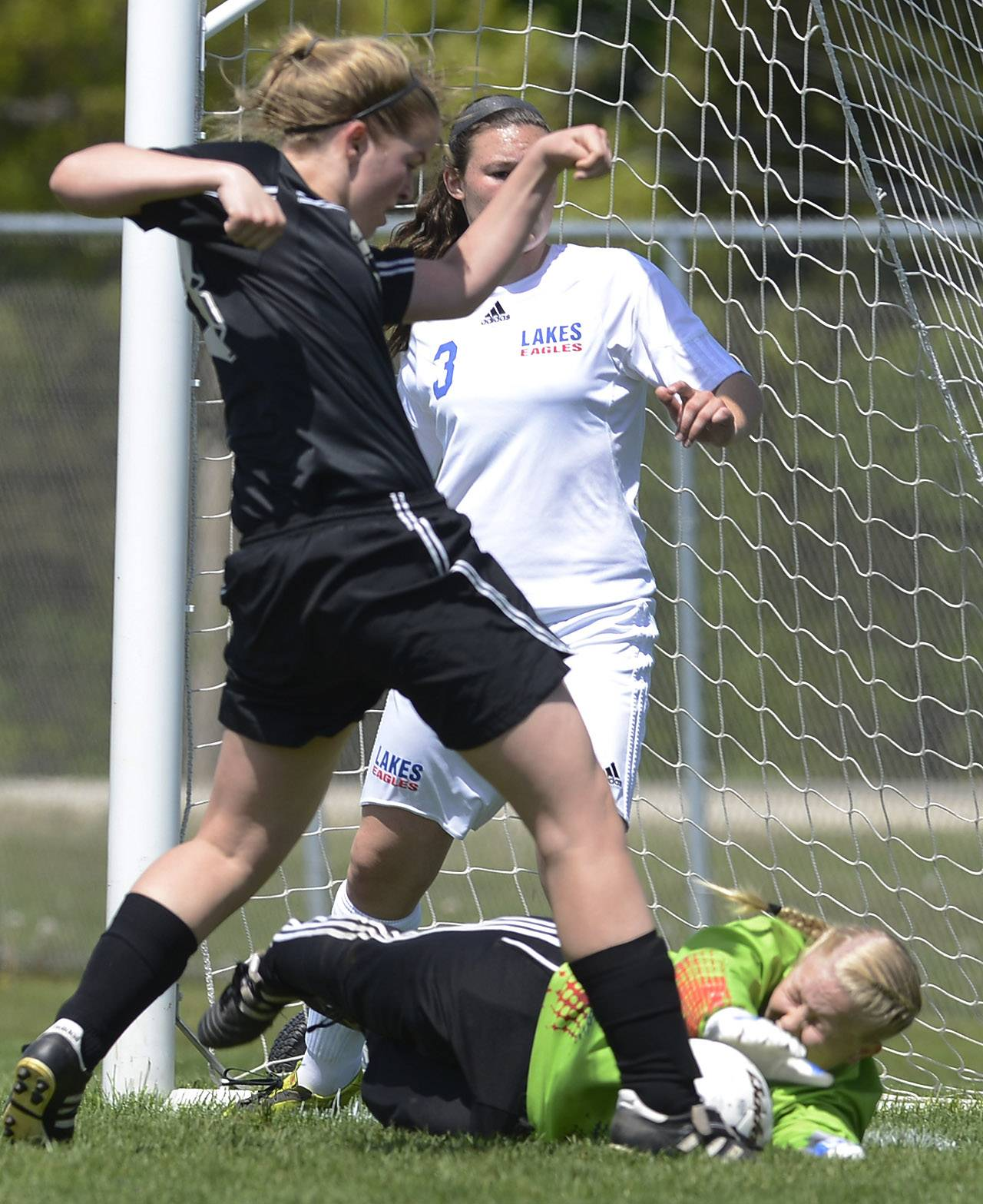Megan Walsh of Prairie Ridge, left, kicks the ball past Lakes goalkeeper Kara Jones for a first-half goal during the Class 2A regional final at Lakes on Saturday.