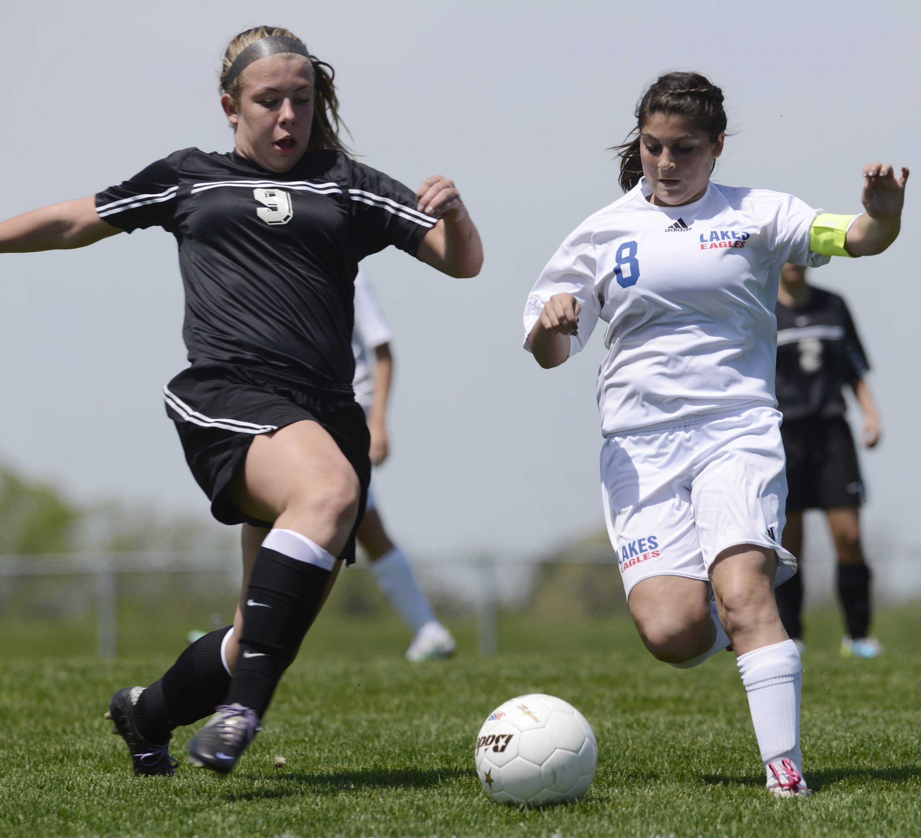 Alexis Petersen of Prairie Ridge, left, and Jessica Cipolla of Lakes pursue the ball during the Class 2A regional final at Lakes on Saturday.