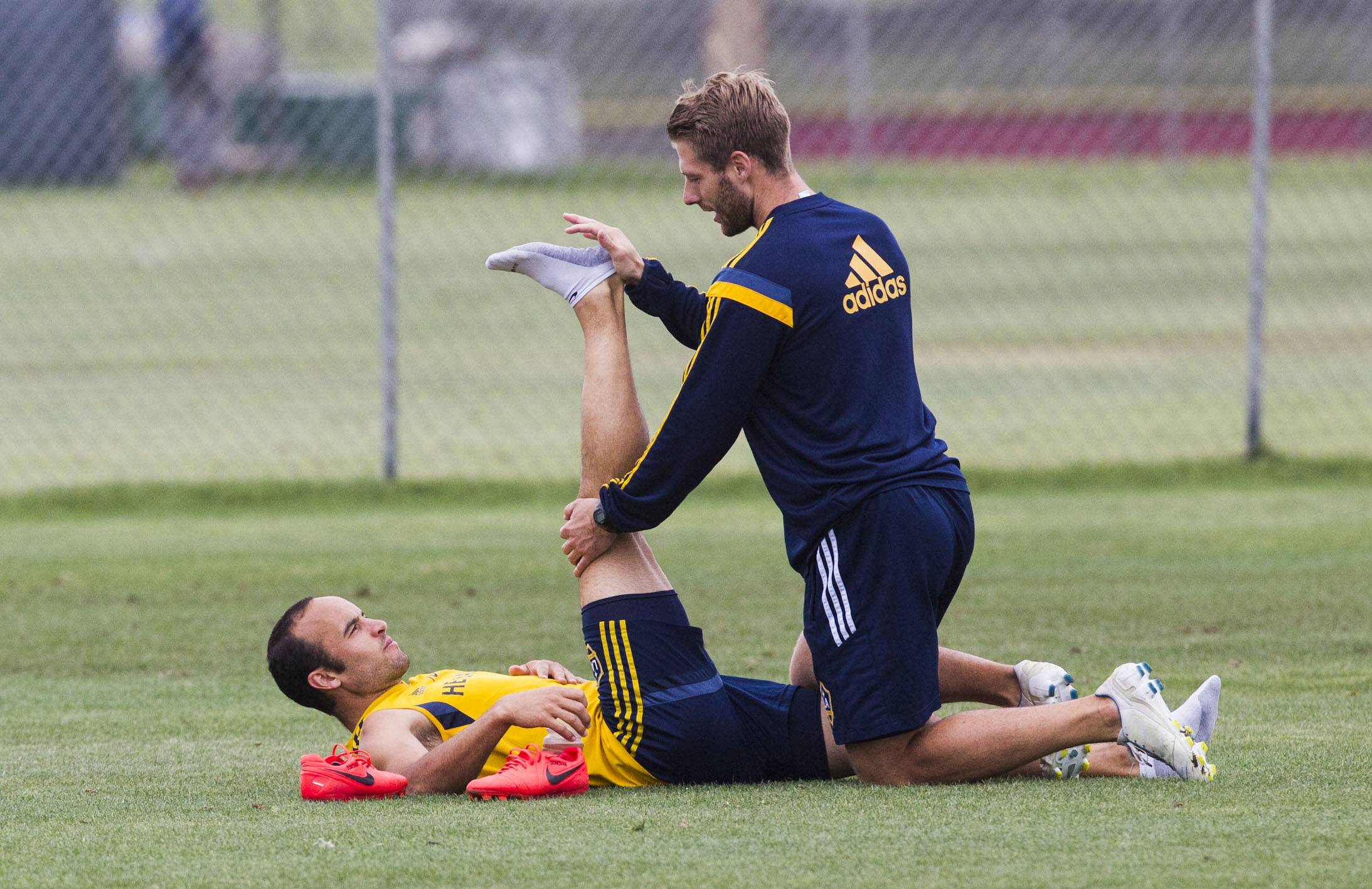 Los Angeles Galaxy forward Landon Donovan is assisted in stretching by trainer Kurt Andrews during a training session at StubHub Center in Carson, Calif., Saturday, May 24, 2014. Donovan, the most accomplished American player in the history of men's soccer, won't be going to his fourth World Cup. The 32-year-old attacker was among seven players cut Thursday when coach Jurgen Klinsmann got down to the 23-man limit well before the June 2 deadline.
