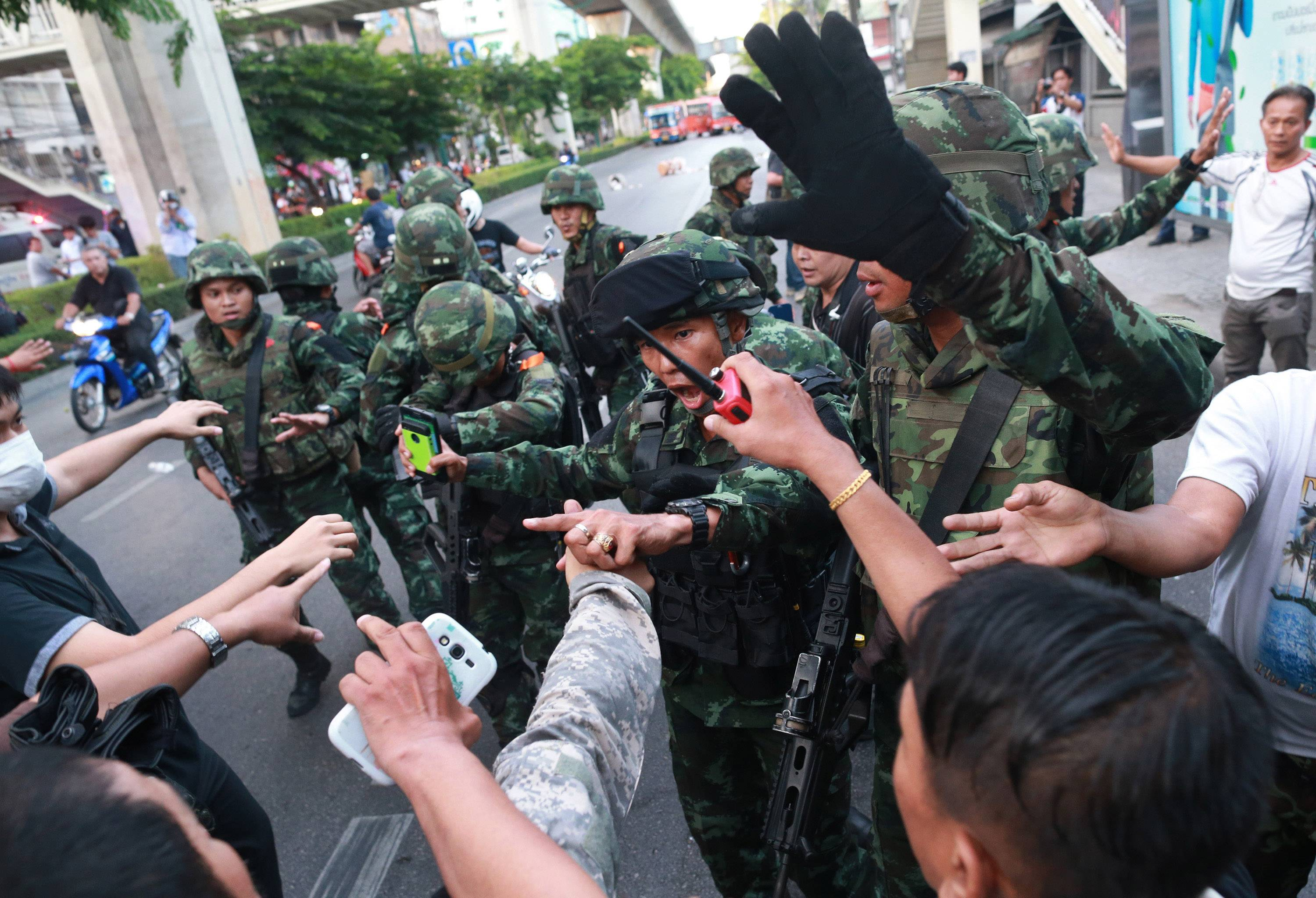 "Thai soldiers scuffle with protesters during an anti-coup demonstration at the Victory Monument in Bangkok, Thailand, Saturday, May 24. Thailand's coup leaders said Saturday that they would keep former Prime Minister Yingluck Shinawatra, Cabinet members and anti-government protest leaders detained for up to a week to give them ""time to think"" and to keep the country calm. They also summoned outspoken academics to report to the junta."