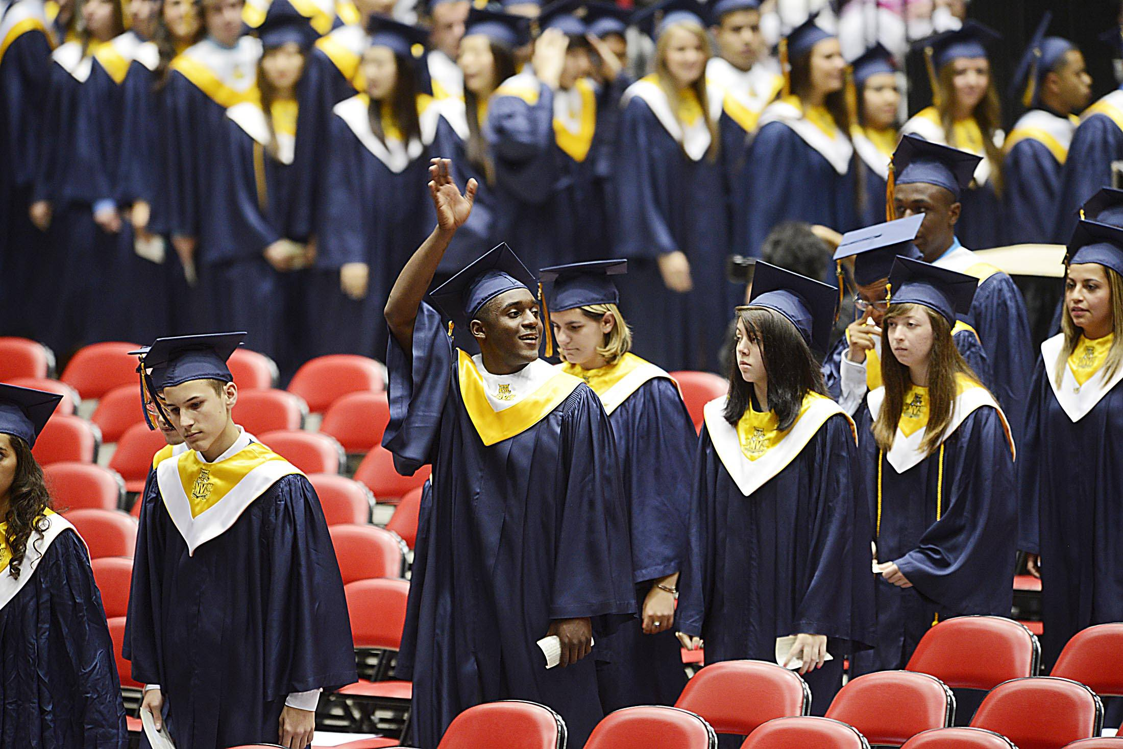Graduate Willie Anderson III waves at family as he enters the arena at the Neuqua Valley High School 2014 commencement exercises at Northern Illinois University Sunday night.